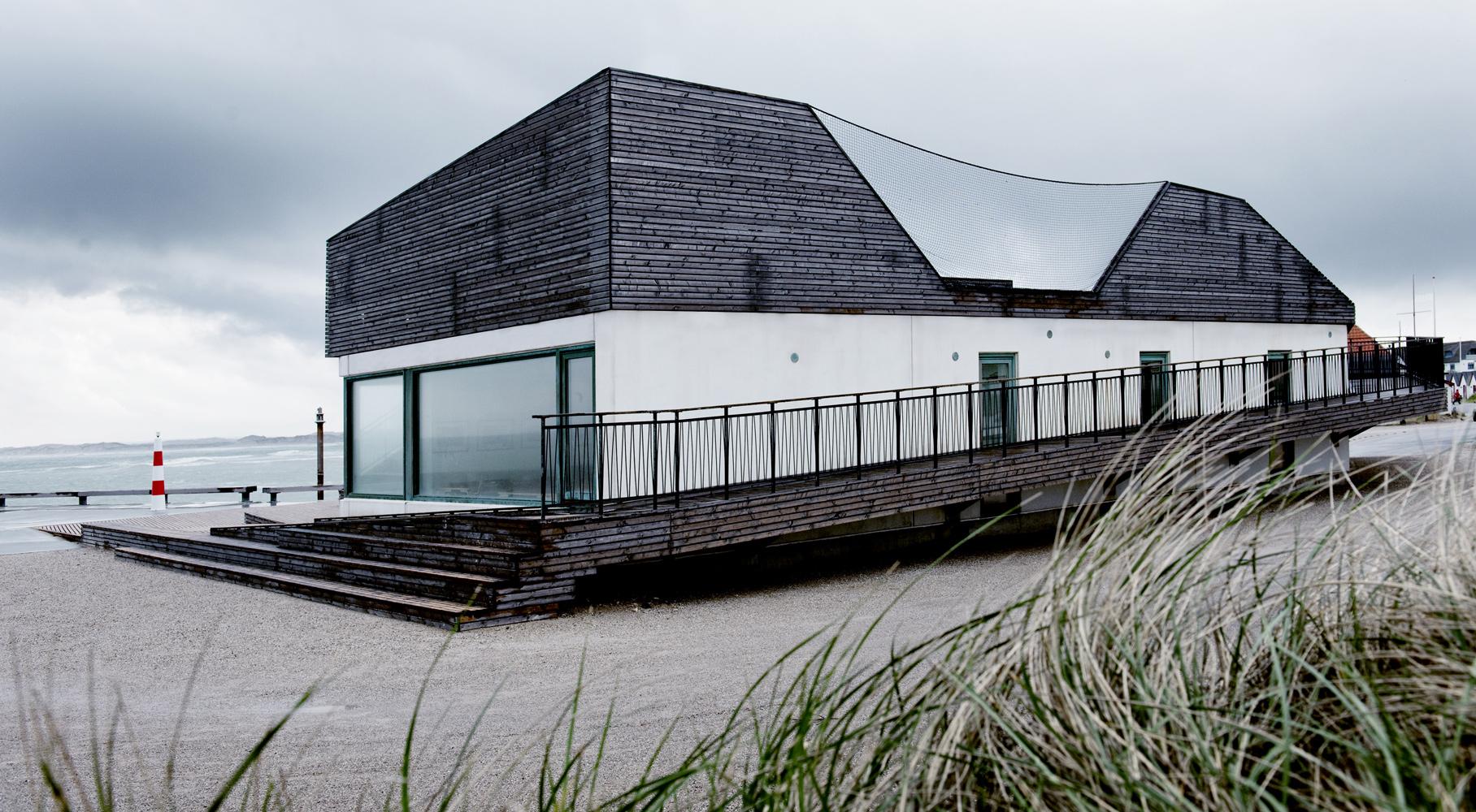 Bygning med rampe i træ, der snor sig rundt om bygning. Beliggende på strand.
