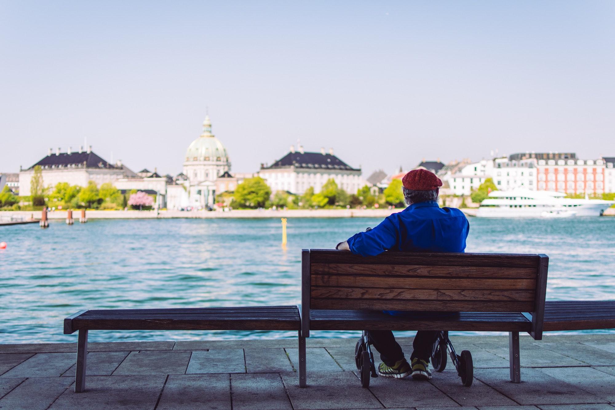 Mand der sidder med bænk med udsigt til vand