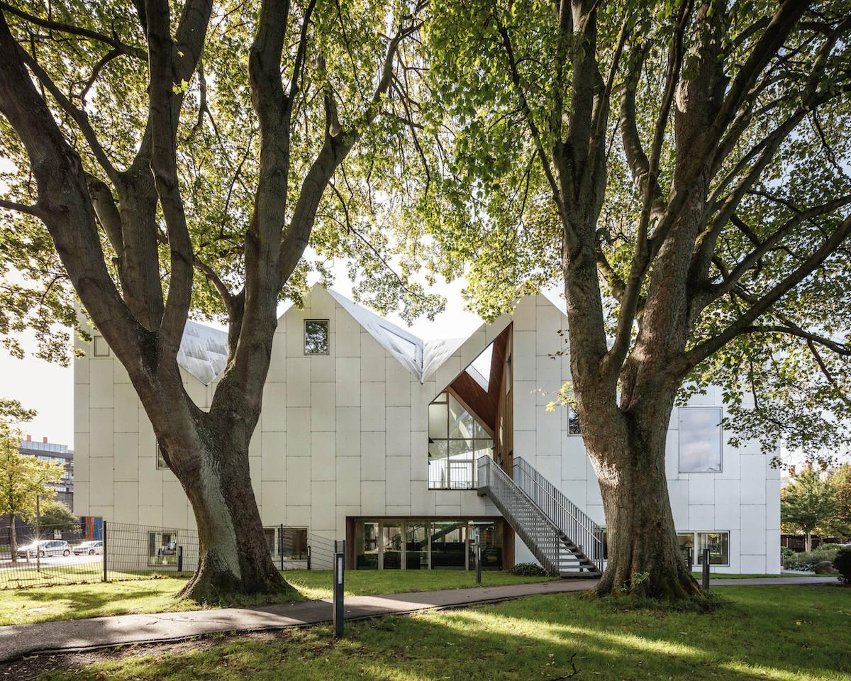 Hvid bygning med trappeopgang. To træer i forgrund.