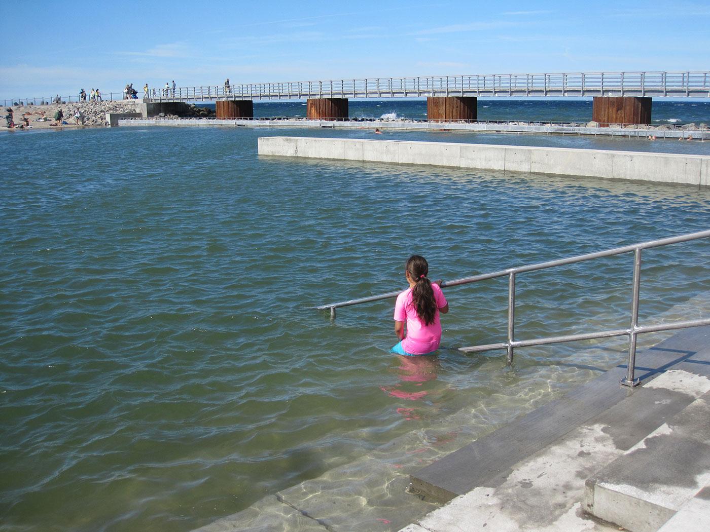 Havnebad med pige der er på vej ned i vand. Pige støtter sig til gelænder. Mole med gående i baggrund.