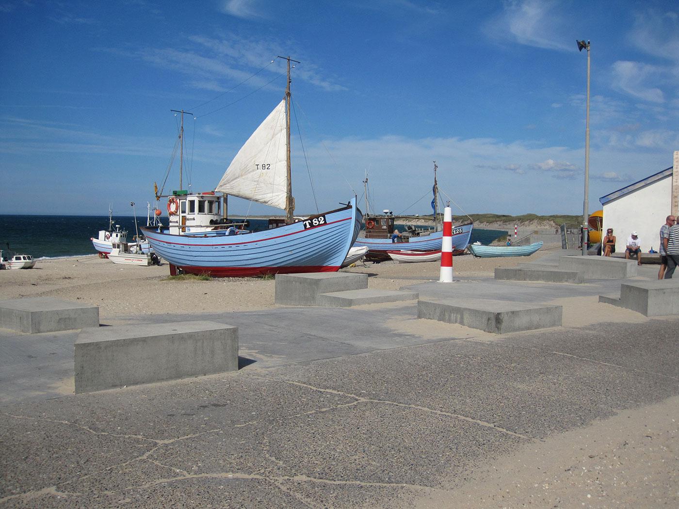 Strand med fiskerbåde i baggrund og fast sti i forgrund. Personer sidder på bænk ved bygning.