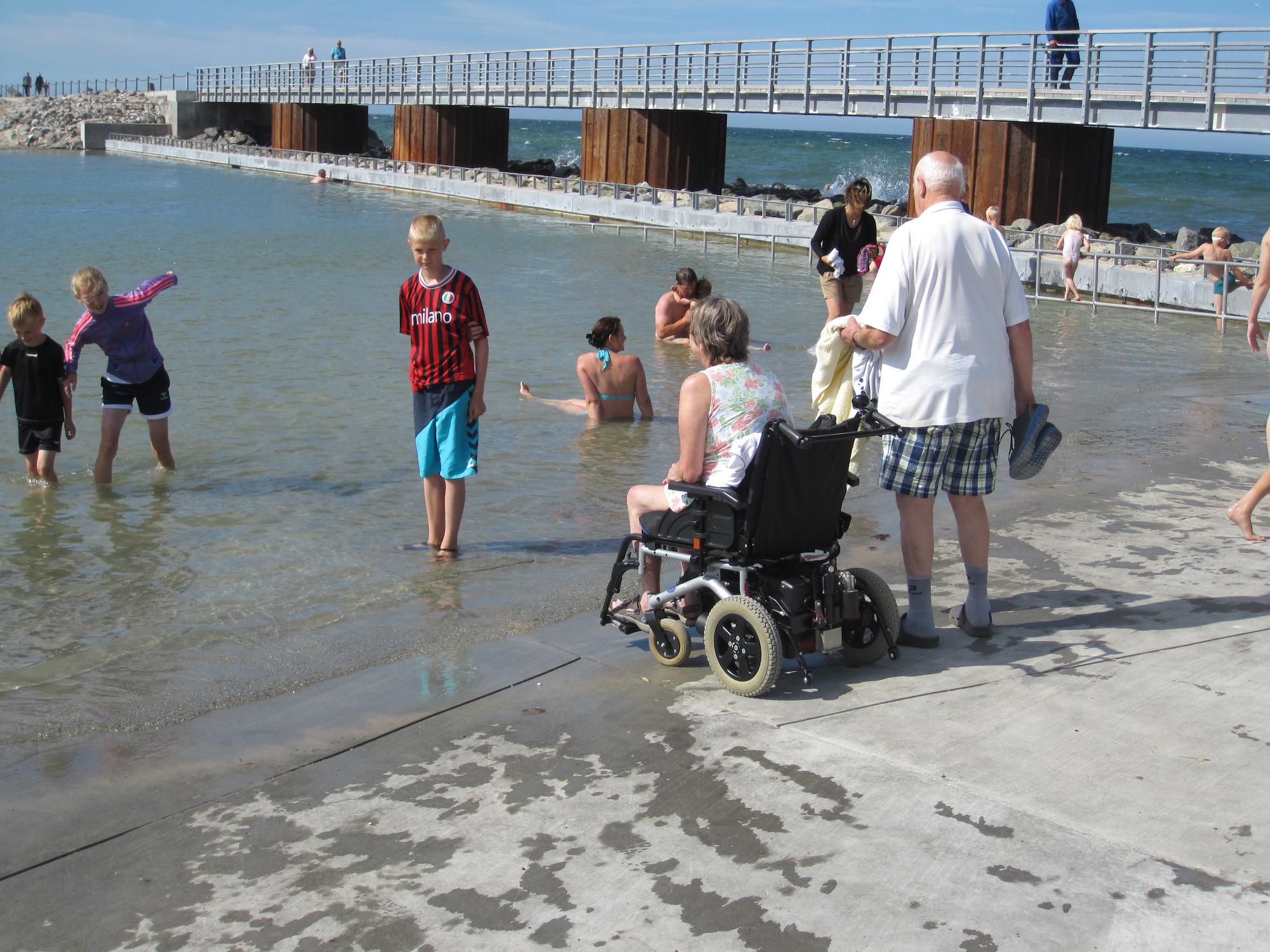 Havnebad med folk der sopper og bader. Dame sidder i kørestol ved vandkanten. Mand står ved siden af med håndklæde og sko i hånden. Mole i baggrund.