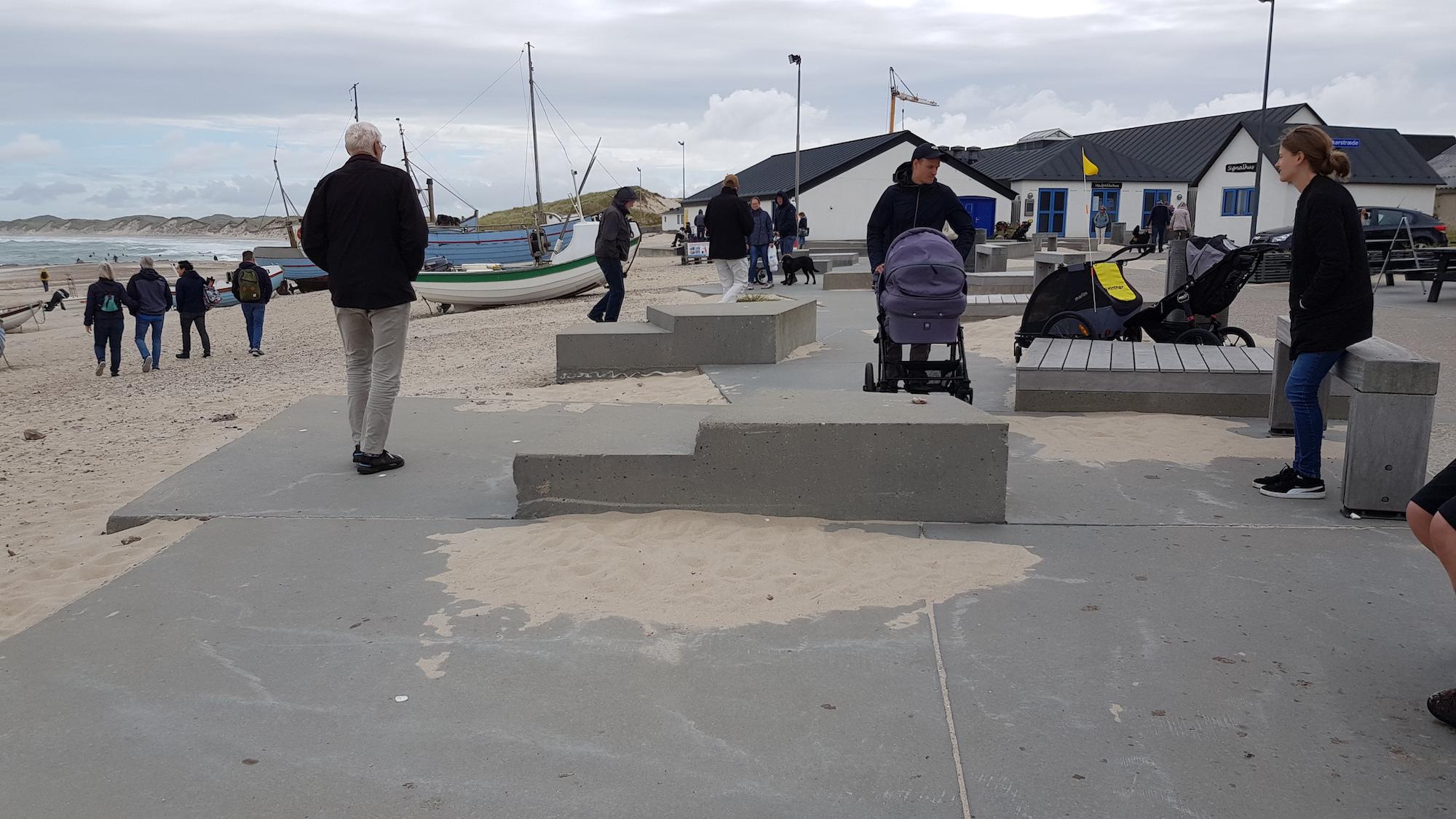 Strand med fiskerbåde og huse samt gående i baggrund. Fast sti i forgrund hvor mand skubber barnevogn, og kvinde står ved bænk. To cykelvogne står parkeret på sti.