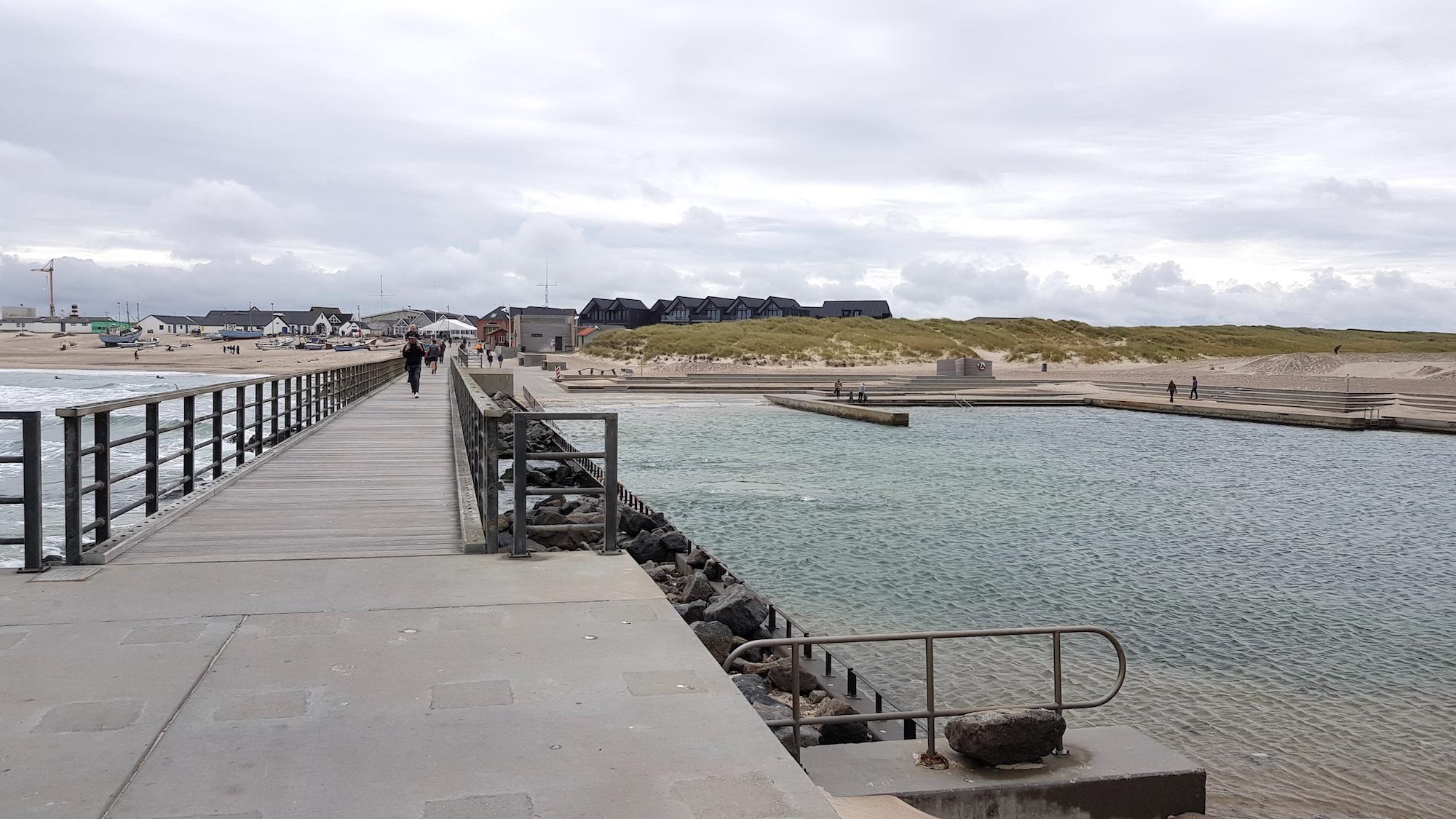 Strand med klitter og huse samt havnebad og mole med gående personer