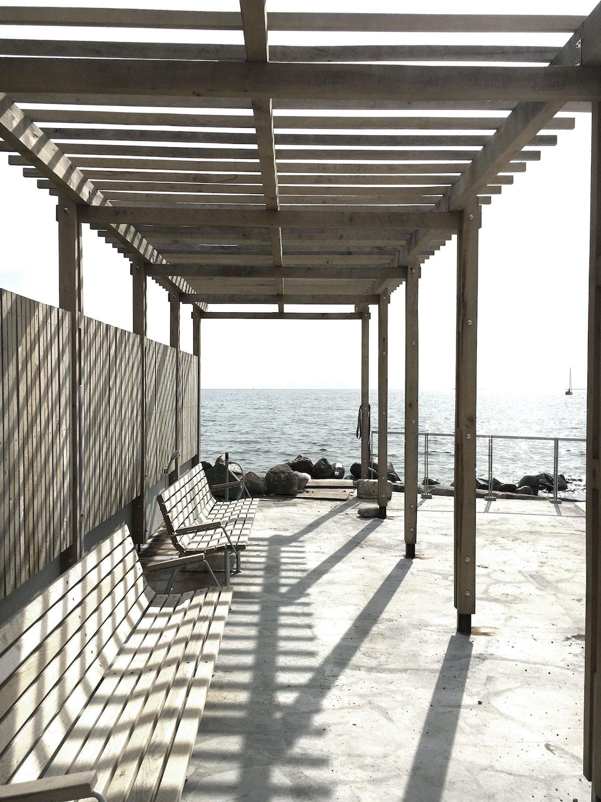 Overdækket terrasse med bænk og udsigt til hav