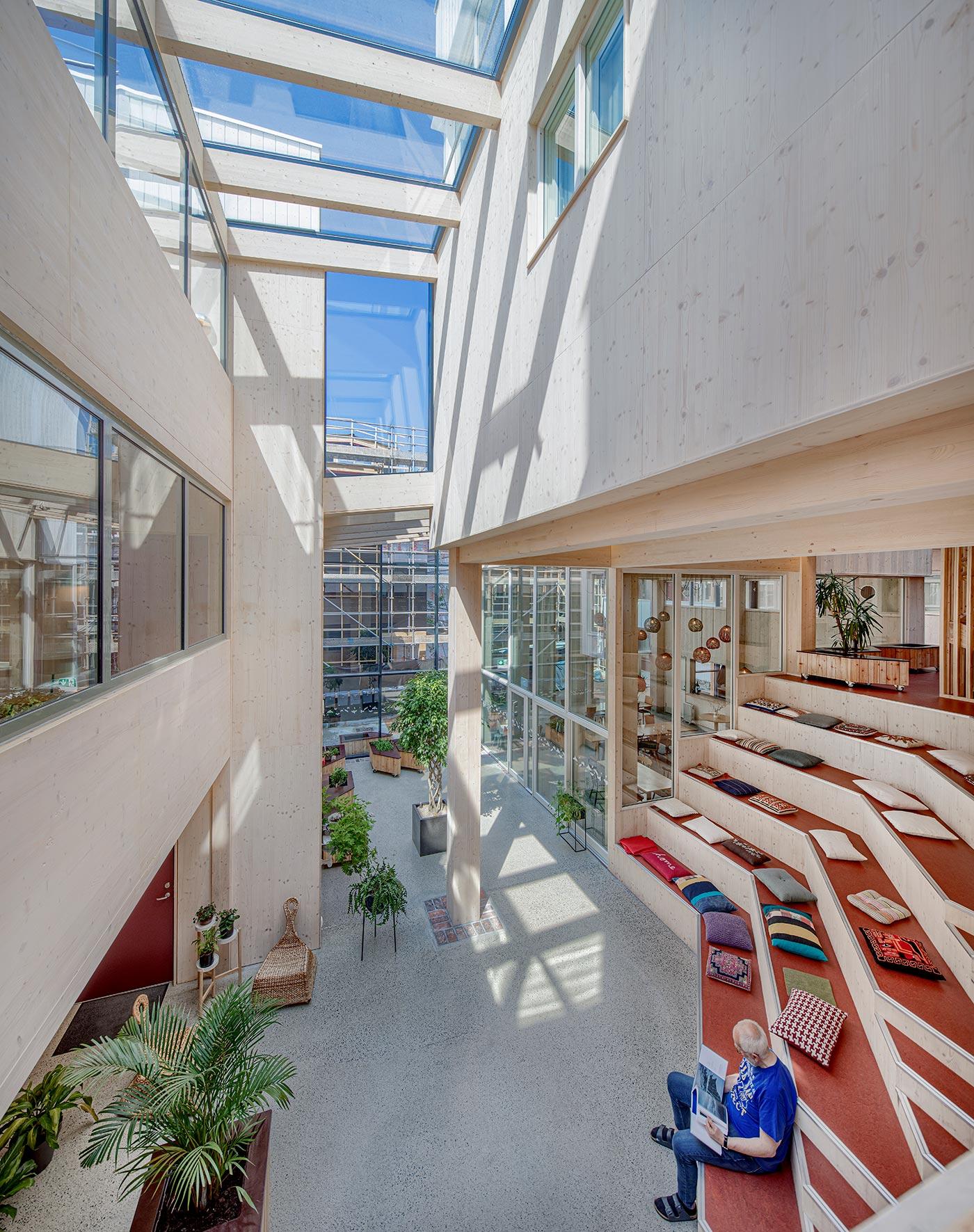 Aflangt rum med højt til loftet og ovenlysvinduer. Trappe i flere niveauer med puder hvor mand sidder og kigger i bog. Rundt i rummet er placeret grønne planter.