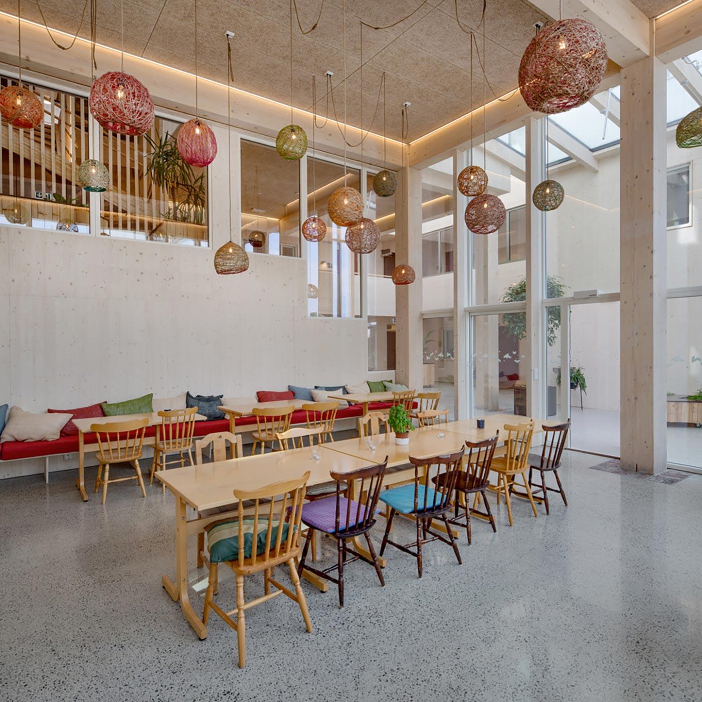 Spisesal med aflange borde samt stole og lang bænk med puder. Farverige lamper hænger ned fra loftet. Vinduesglas fra gulv til loft adskiller spisesalen fra rummet ved siden af