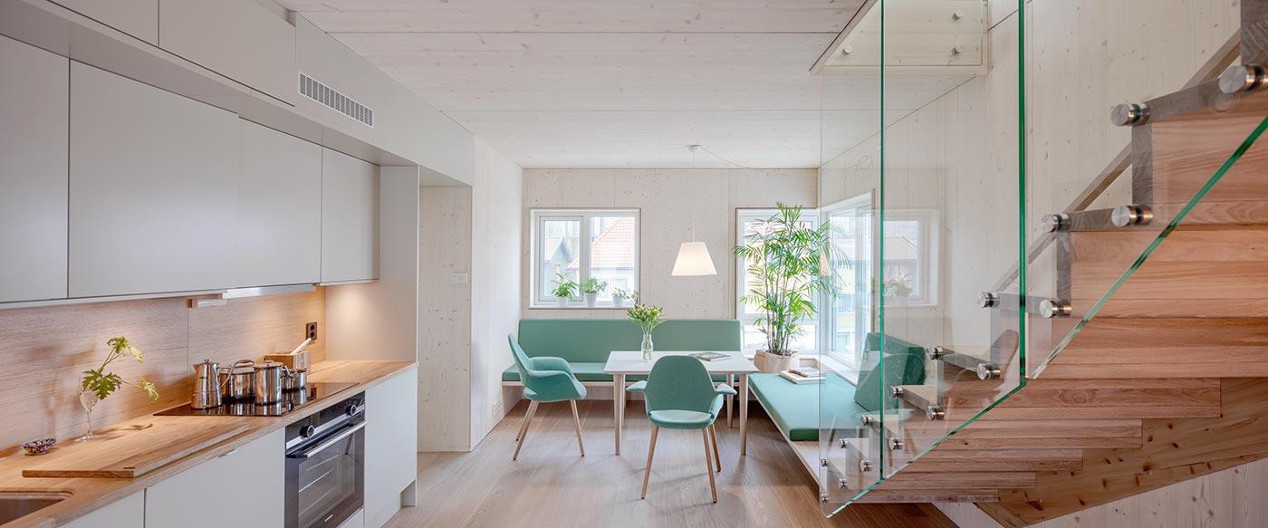 Køkken alrum med aflangt køkkenbord samt spiseområde med bænke, stole og spisebord. Trappe fører op til næste sal.