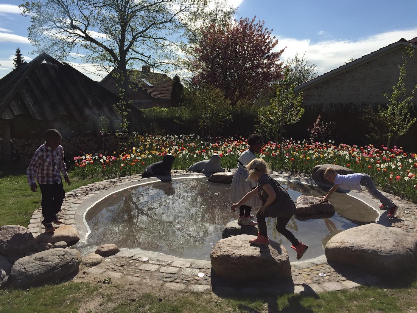 Soppebassin med vand omkrænset af små og store sten, hvorpå fire børn leger. Tulipaner i baggrunden
