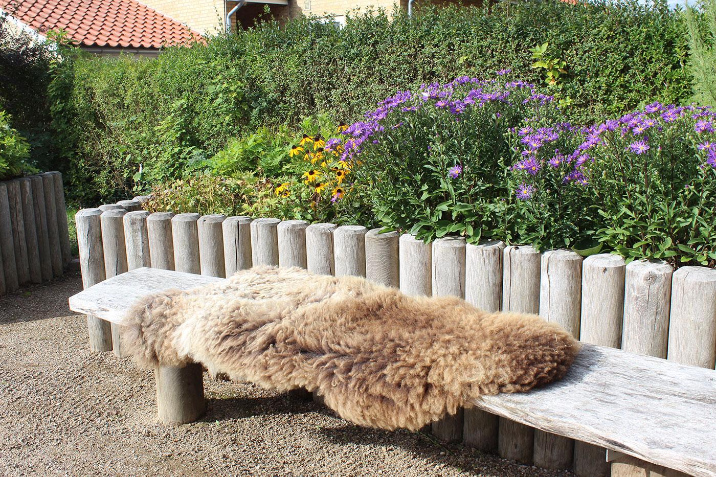 Træbænk står foran blomsterbed. På bænk ligger lammeskind.