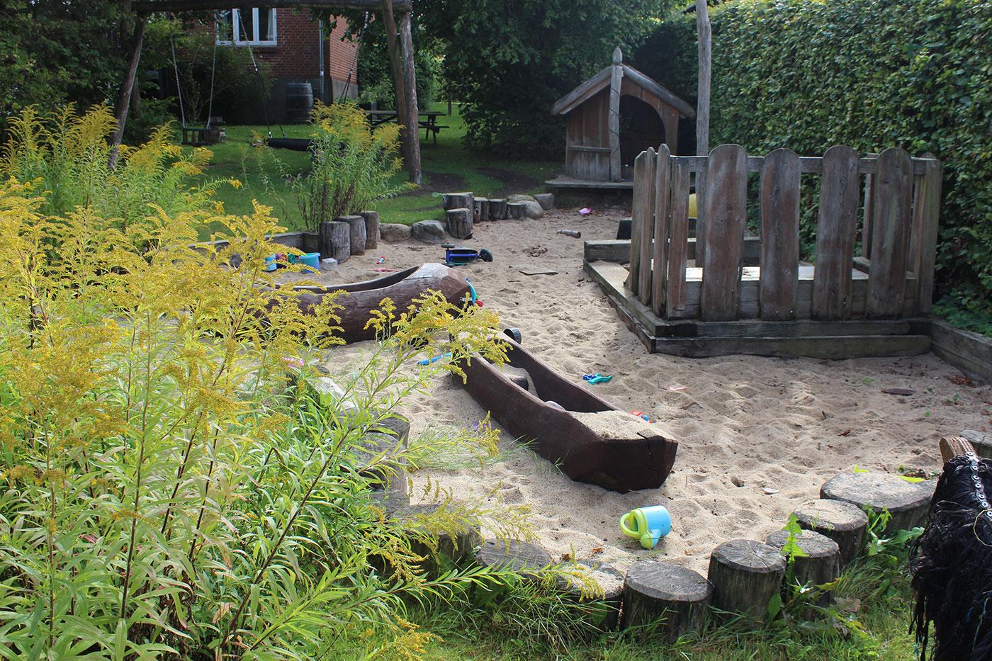 Legeplads i indrammet sandområde. På legepladsen er et legehus i træ og to kanoer i træ. Der ligger legetøj i sandet.
