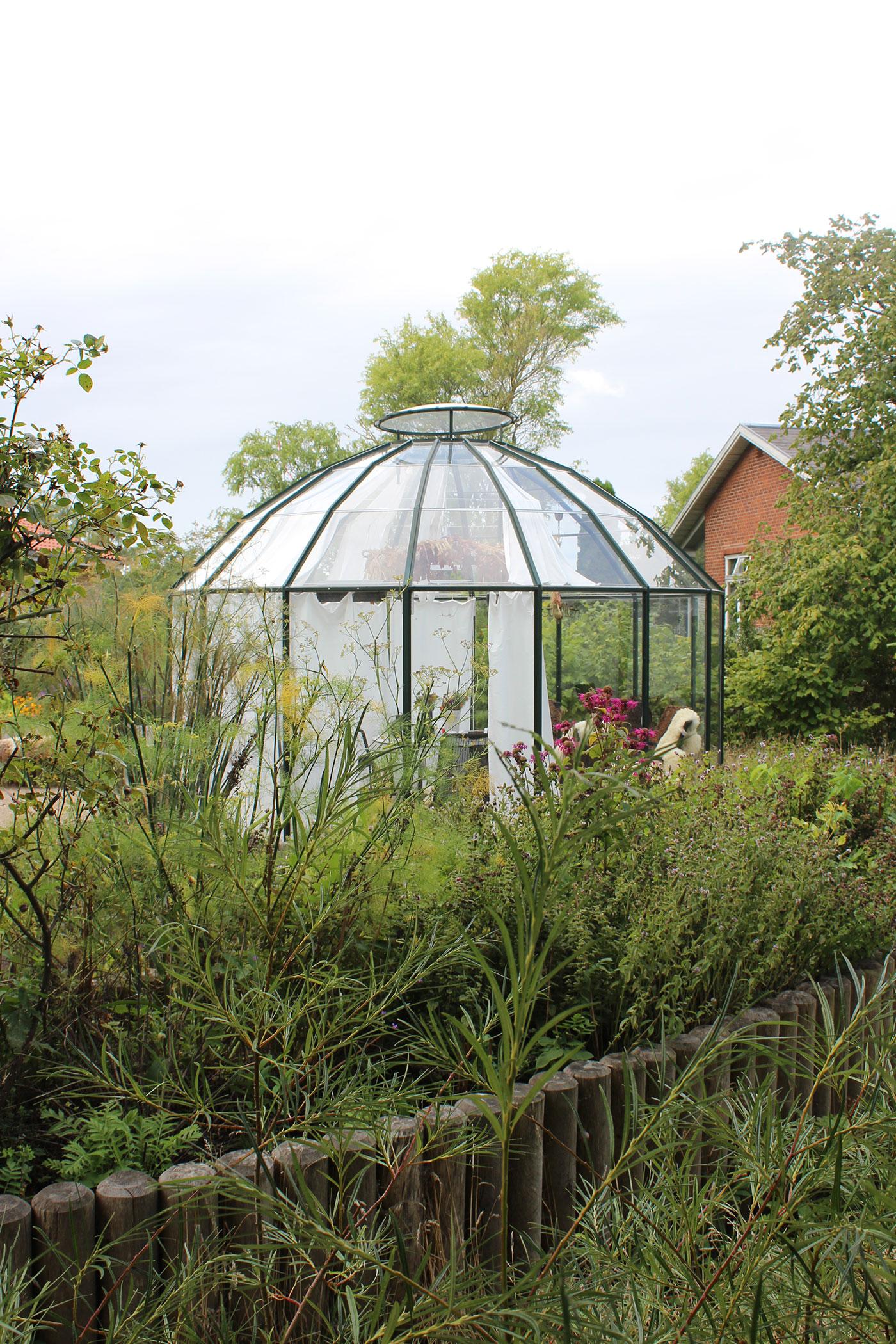 Pavillion i tæt-bevokset have. Der hænger hvide gardiner inde i pavillionen.