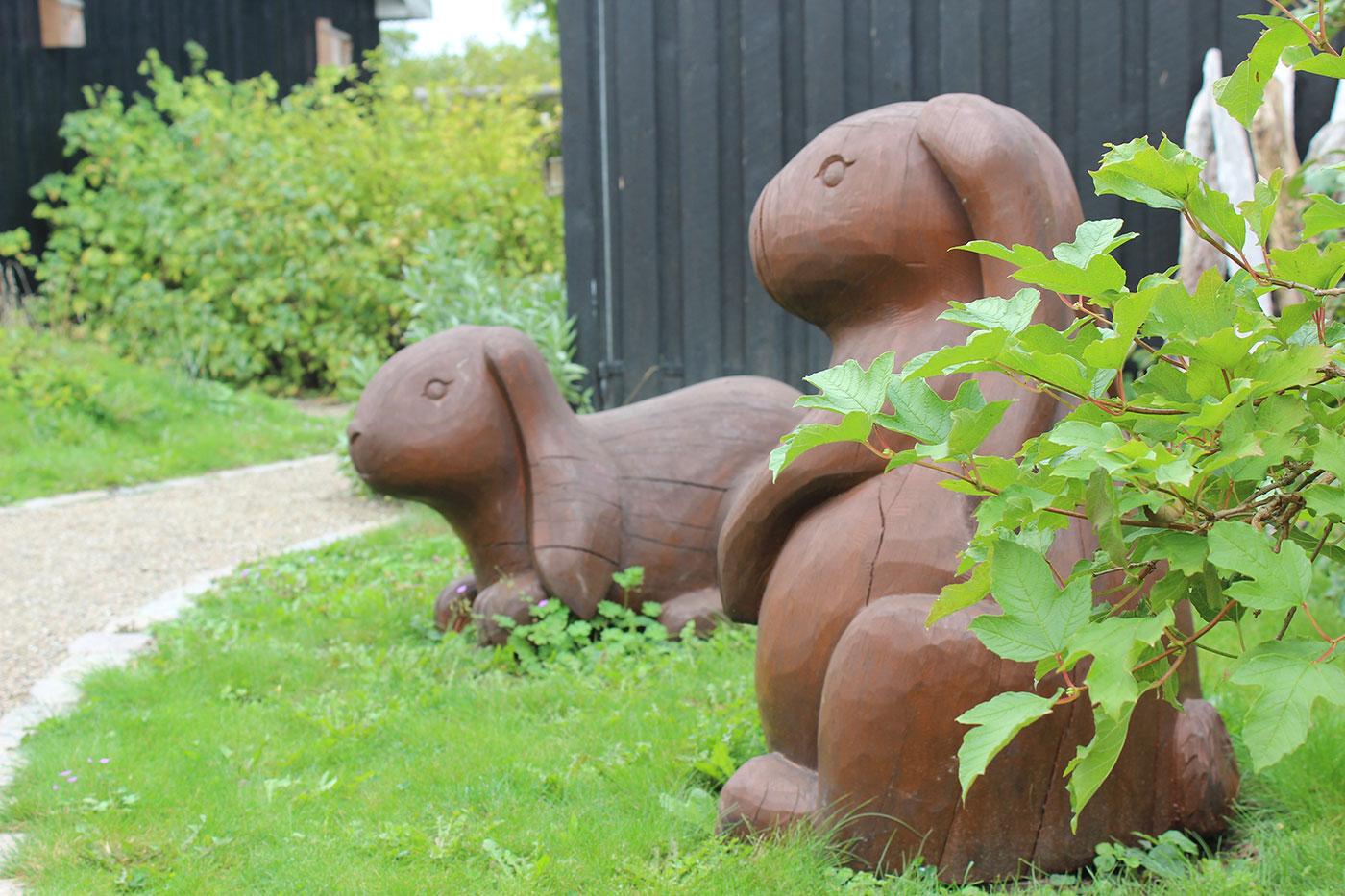 To brune kaninfigurer i træ står på en græsplæne ved en sti. En sort træbygning i baggrunden