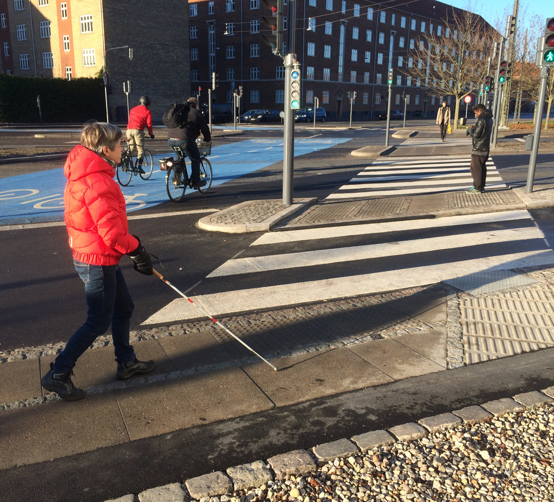 Fodgængerfelt ved et lyskryds. Her er opmærksomheds- og retningsfelter på fortovet, så mennesker med synshandicap kan krydse vejen på egen hånd.