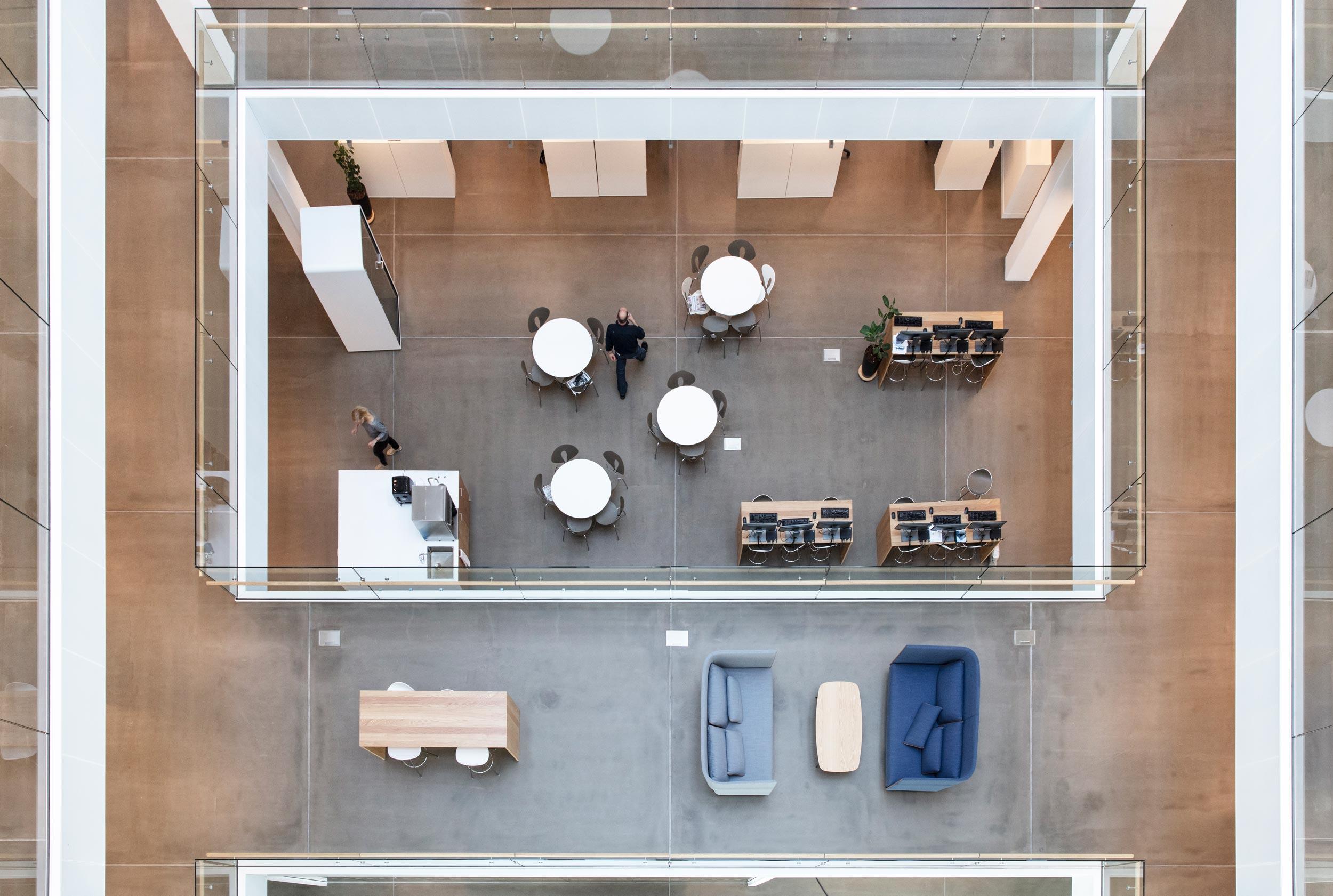 Det indvendige af bygning set oppe fra med borde, stole og lænestole på etagerne under