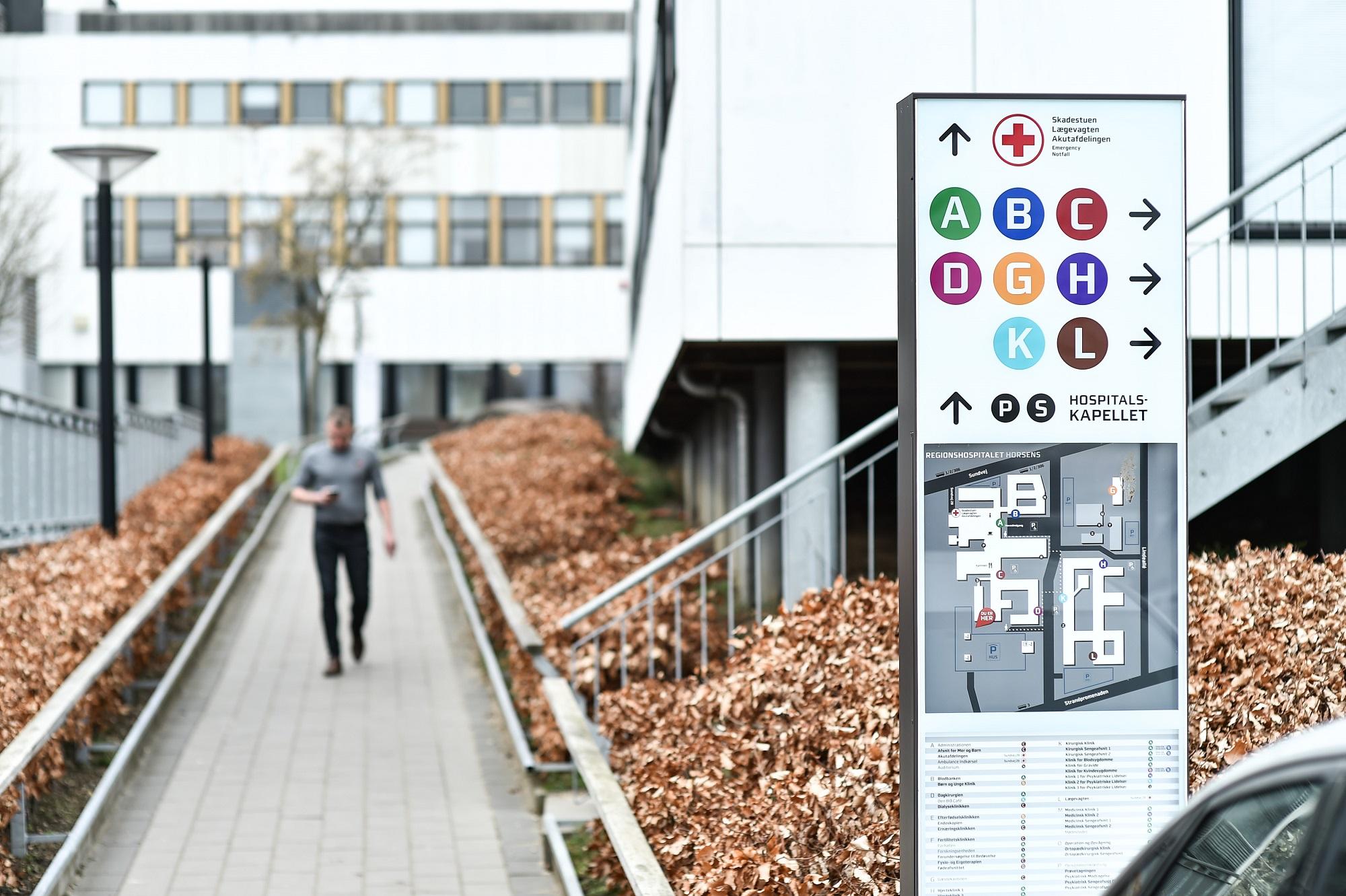 En sti ved indgangen til et hospital. Til højre er der et oversigtskilt.
