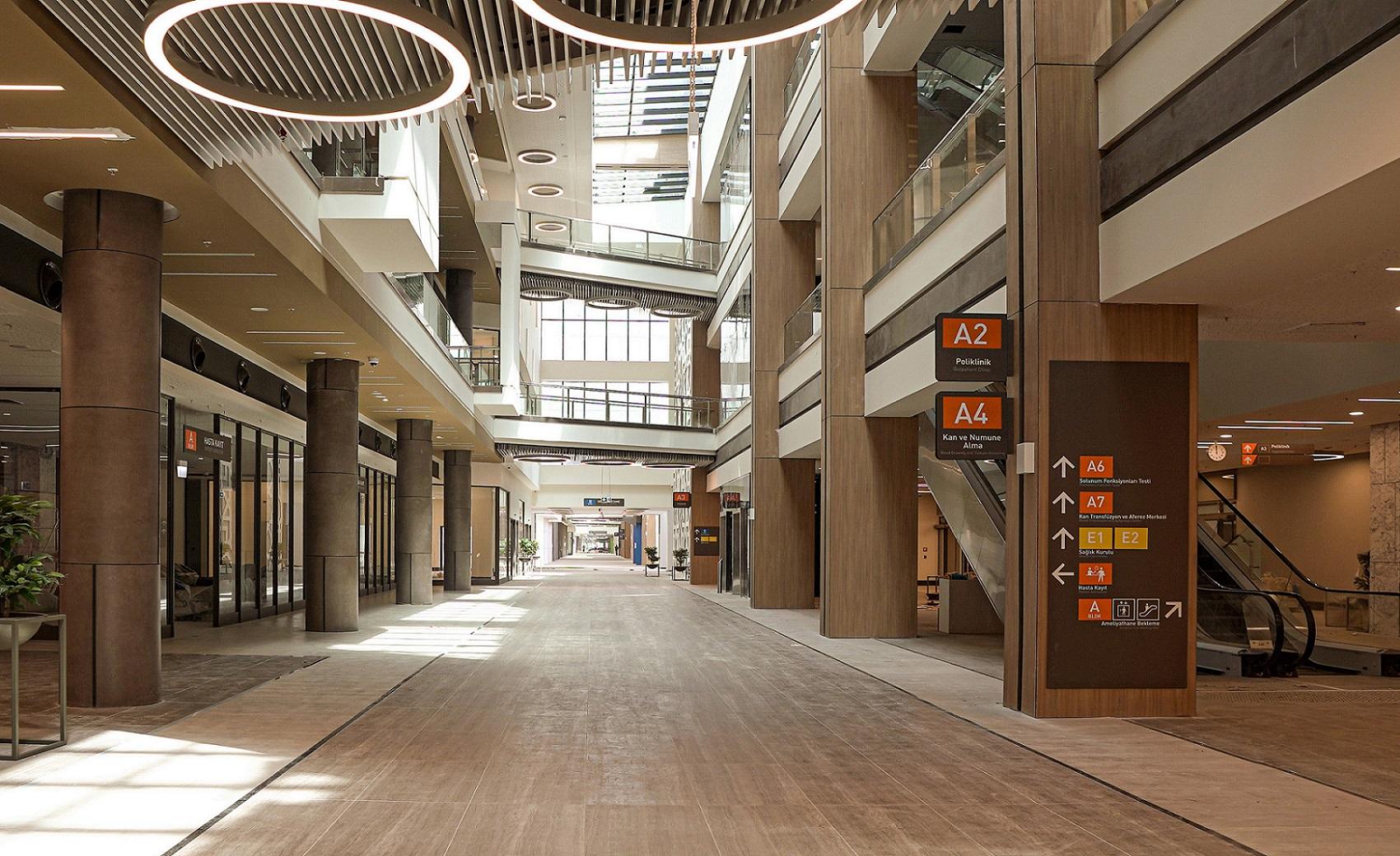 Kig igennem et atrie med ovenlys og markante søjler. Til højre er der skiltning ifm. en rulletrappe.