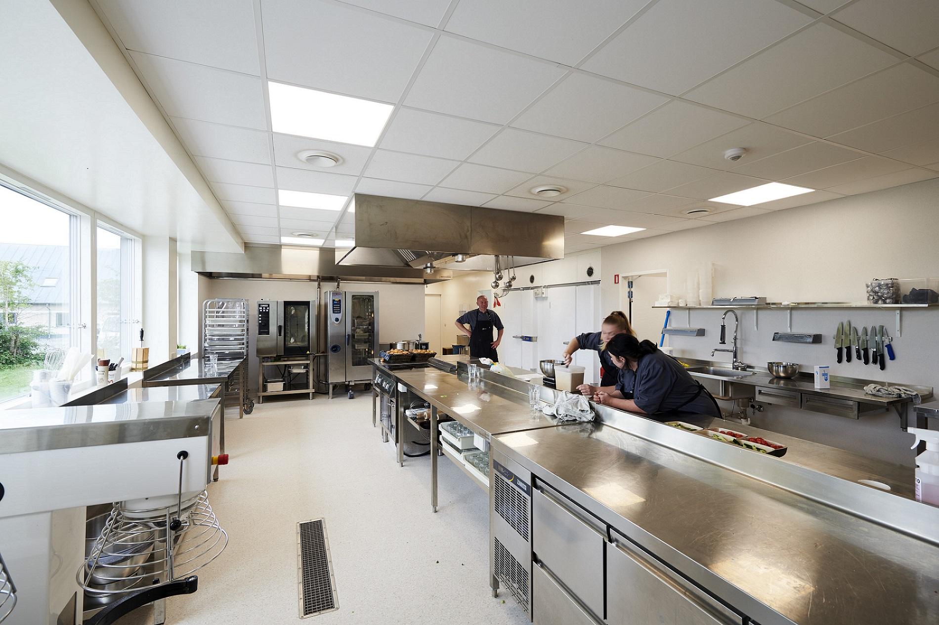 To elever står ved et køkkenbord. I baggrunden står en underviser.