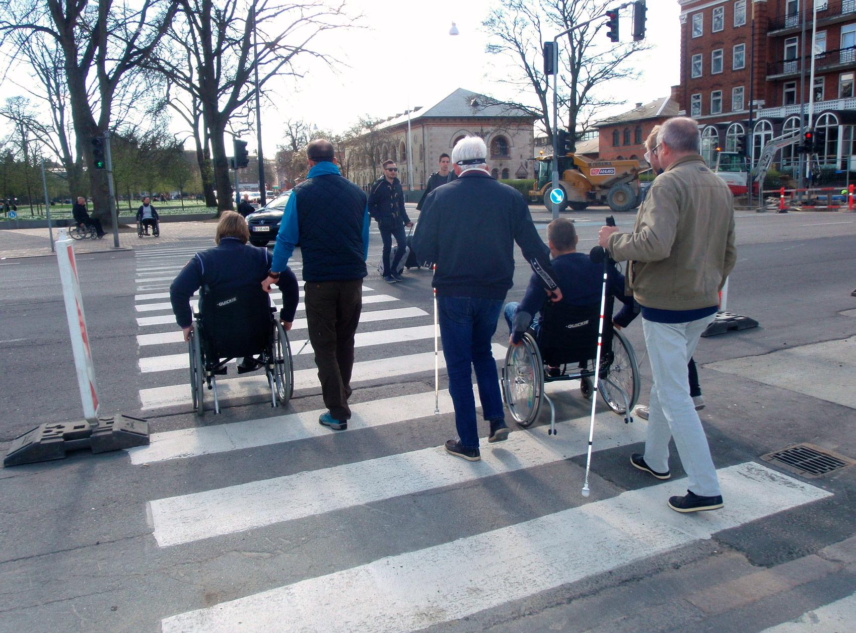 En gruppe på prøv-selv-kursus i kørestol eller med bind for øjnene krydser vejen ved fodgængerovergang