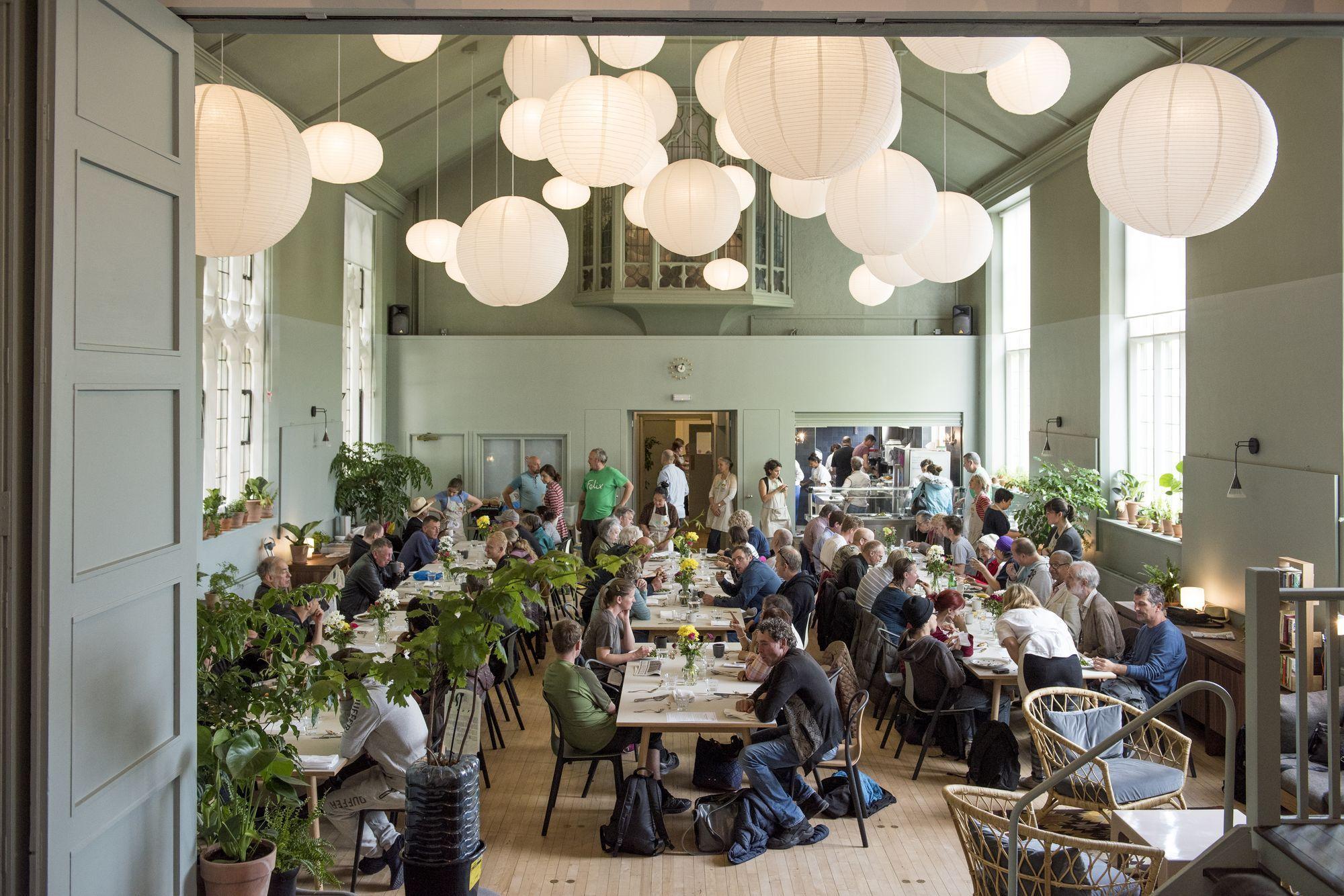 Det store, åbne rum med langborde, der er fint dækket op, under mange store designerlamper, der hænger ned fra loftet.