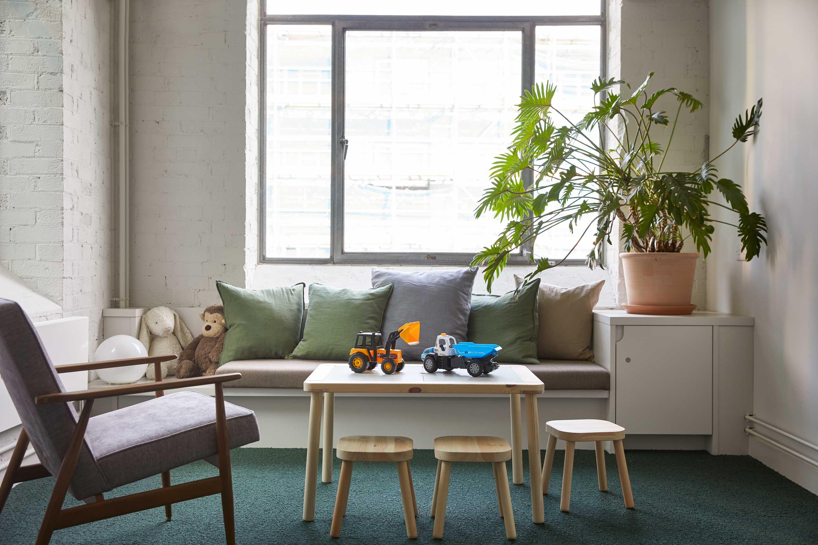 Venteværelse med siddepladser med puder ved vindue, bord med legetøj og en grøn plante.
