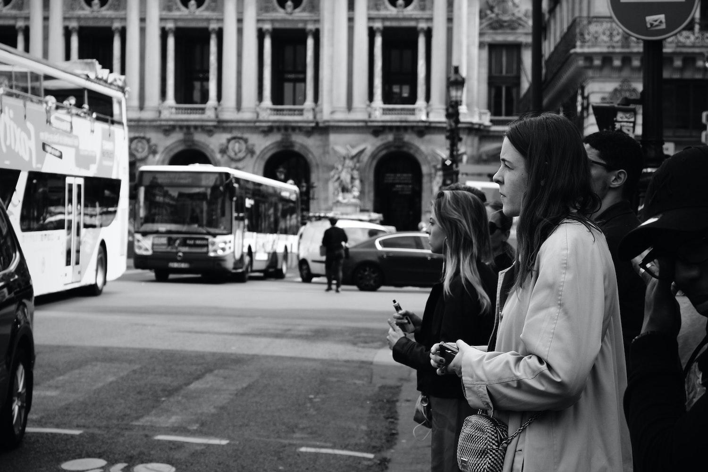 En gruppe af ældre kvinder står og sidder ved et busstoppested