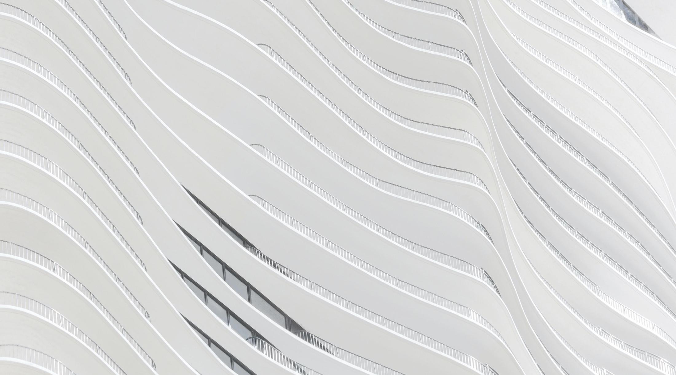 Hvid bygning med bølget front og altaner