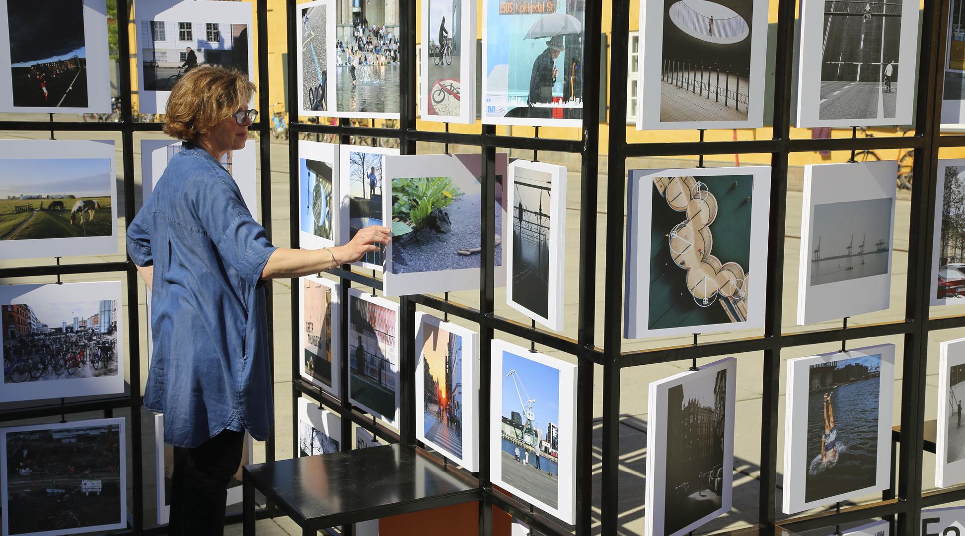 Kvinde kigger på billeder til udendørs fotoudstilling