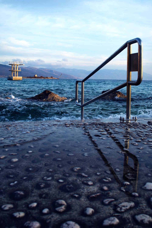 En asfalteret strand med et gelænder, der leder ned i vandet.