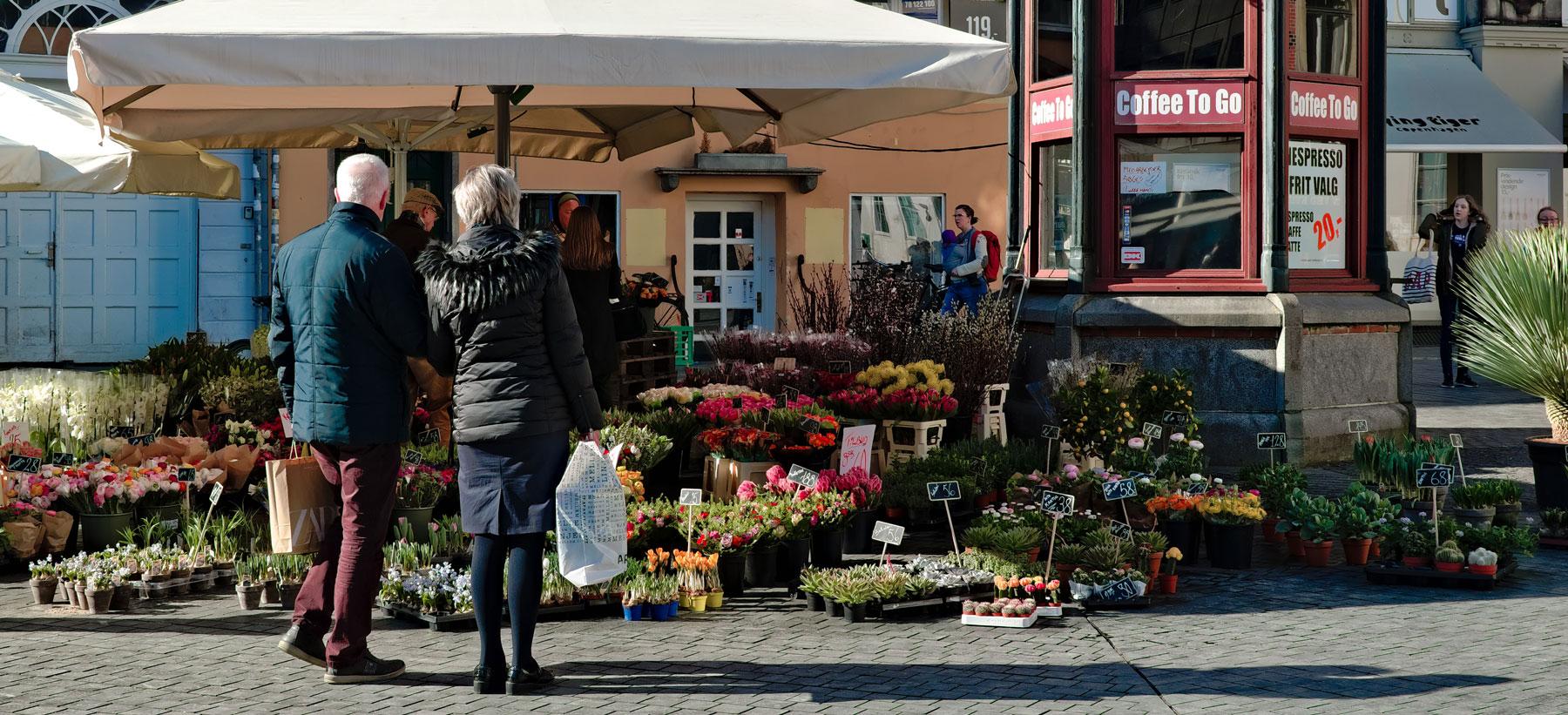 En ældre mand og kvinde står foran en blomsterhandler