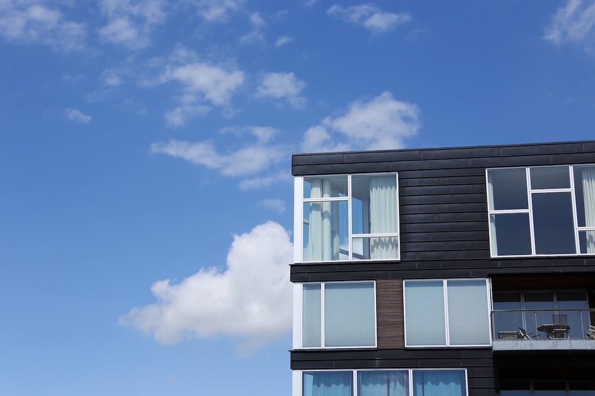 De øverste etager med vinduer og altan i hjørne af bygning. Blå himmel