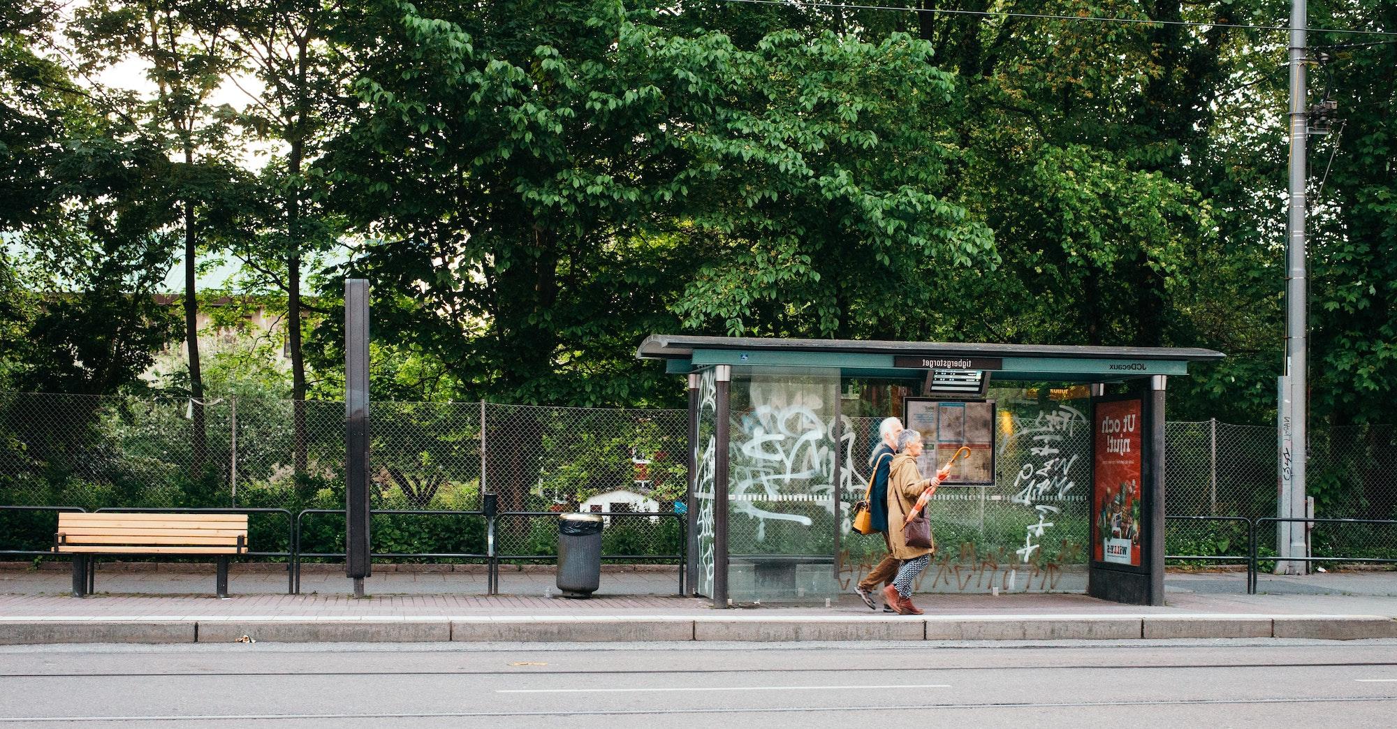 To ældre personer går forbi et busstoppested, der har en høj kantsten ud til busbanen