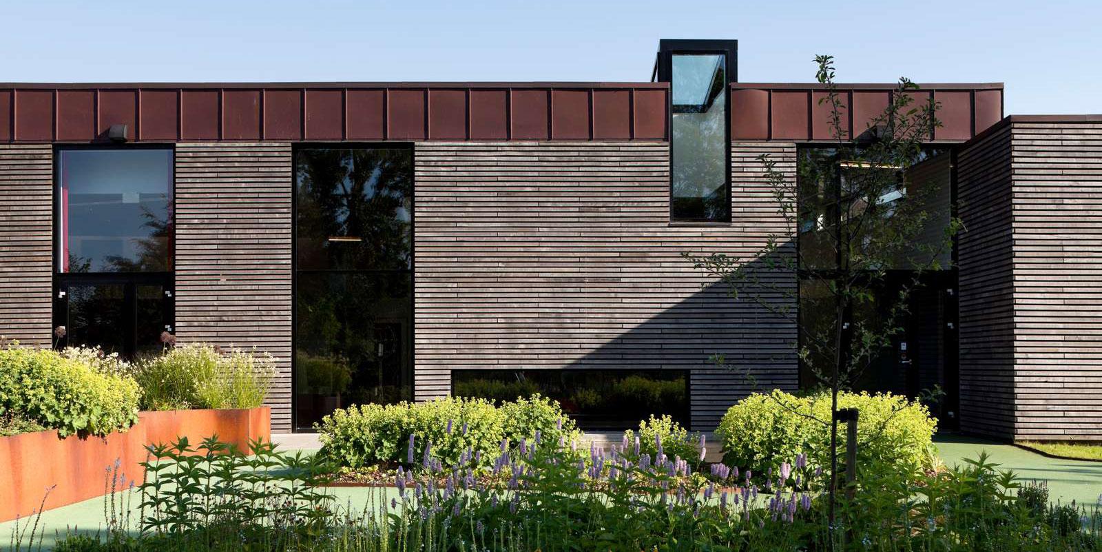 Bygning med vinduer, kobbertag og træfacade og grønne planter foran