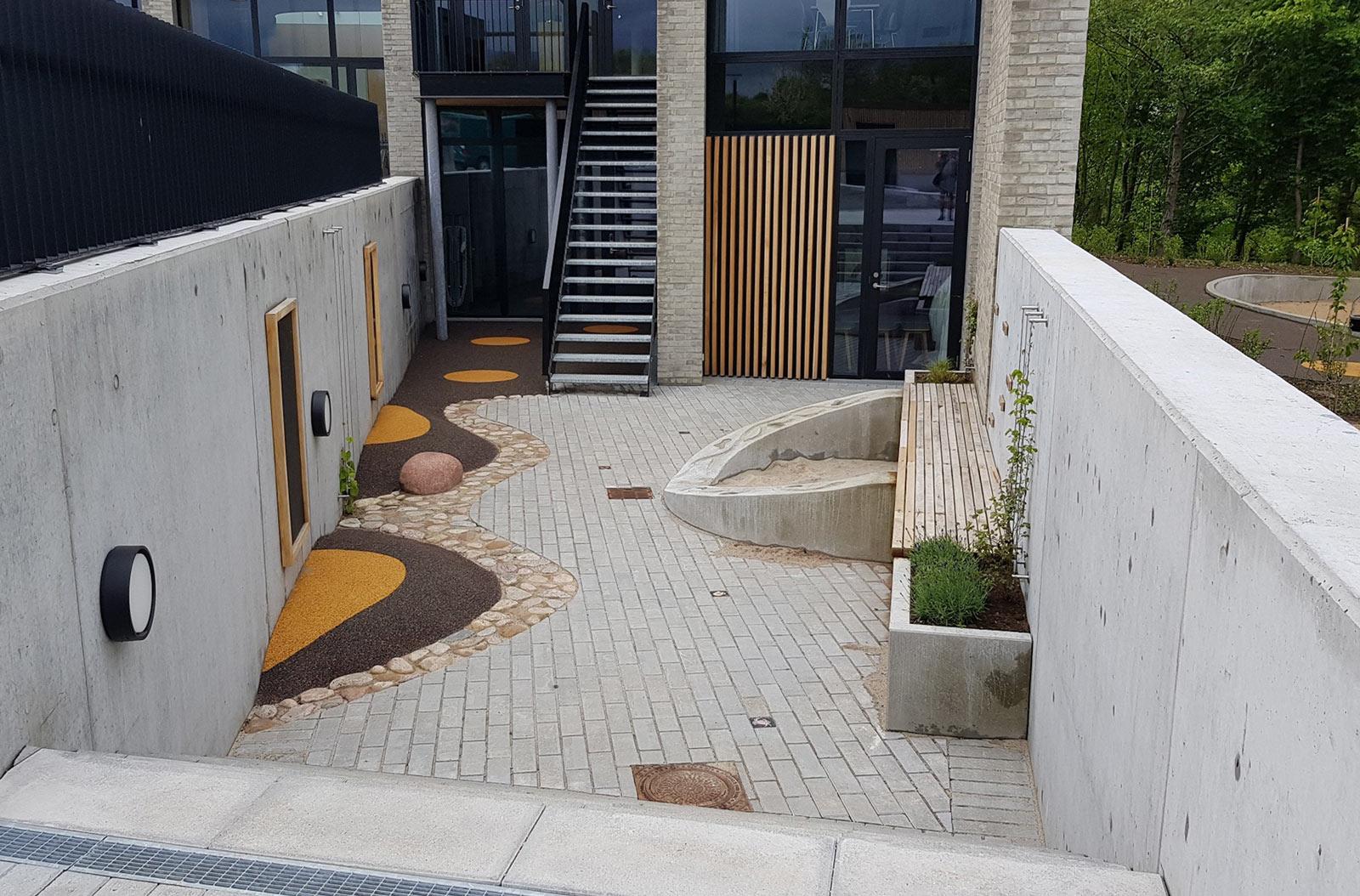 En trappe går fra en bygning ned til et område hvor der er en bænk og flisebelægning