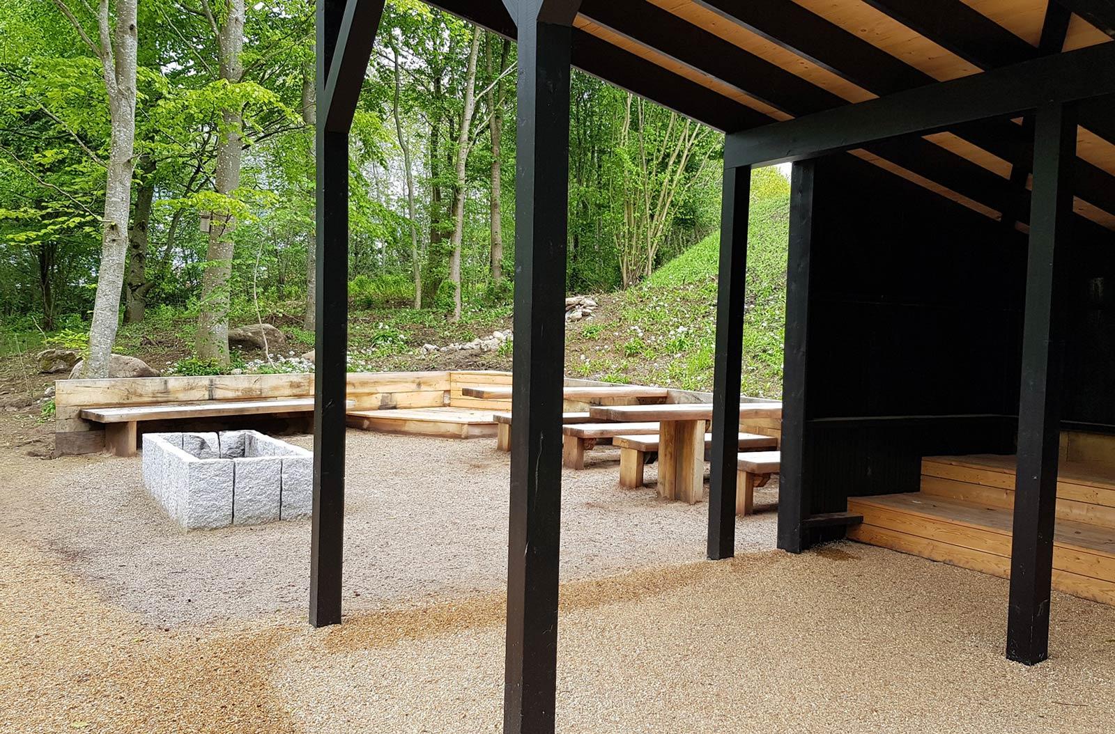 En bålplads med bord og bænke og et overdækket område i træ