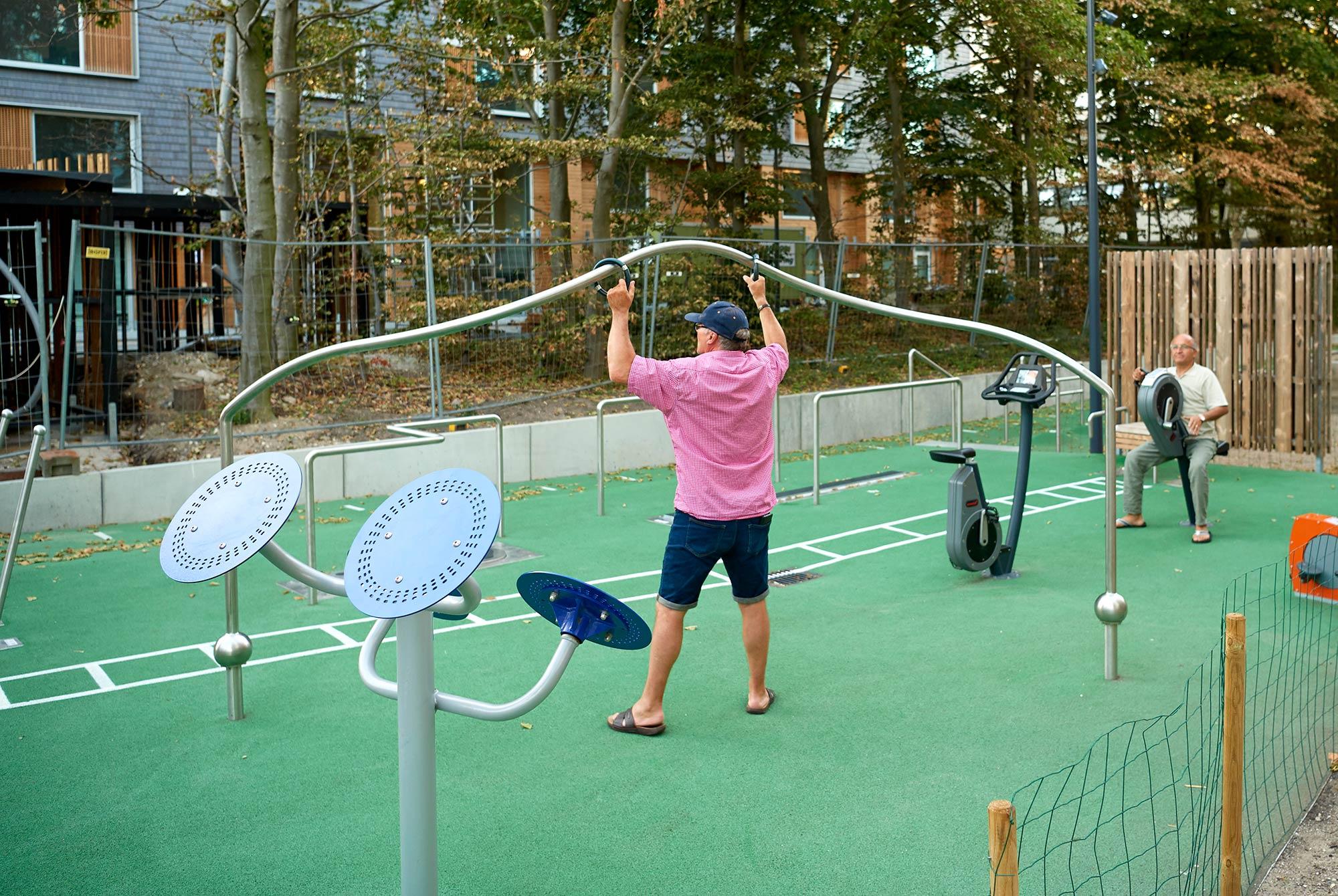 Område med træningsredskaber hvor to mænd træner. Den ene strækker armene og holder ved to ringe, som køres rundt på en skinne, den anden sidder og styrer to pedaler med hænderne.