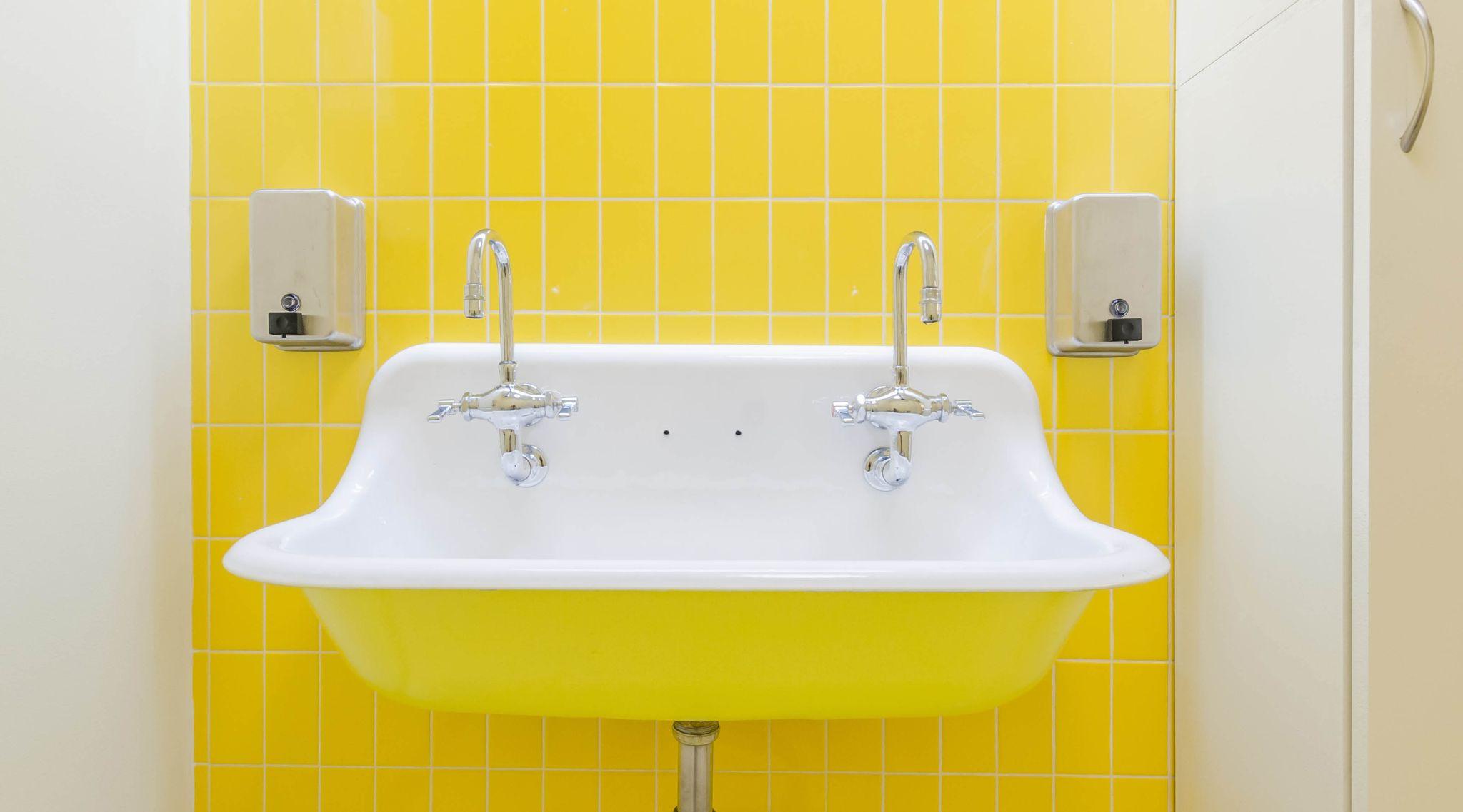 Gul og hvid håndvask i porcelæn med to armaturer. Håndvask hænger på væg med gule klinker og til højre og venstre hænger to sæbedispensere