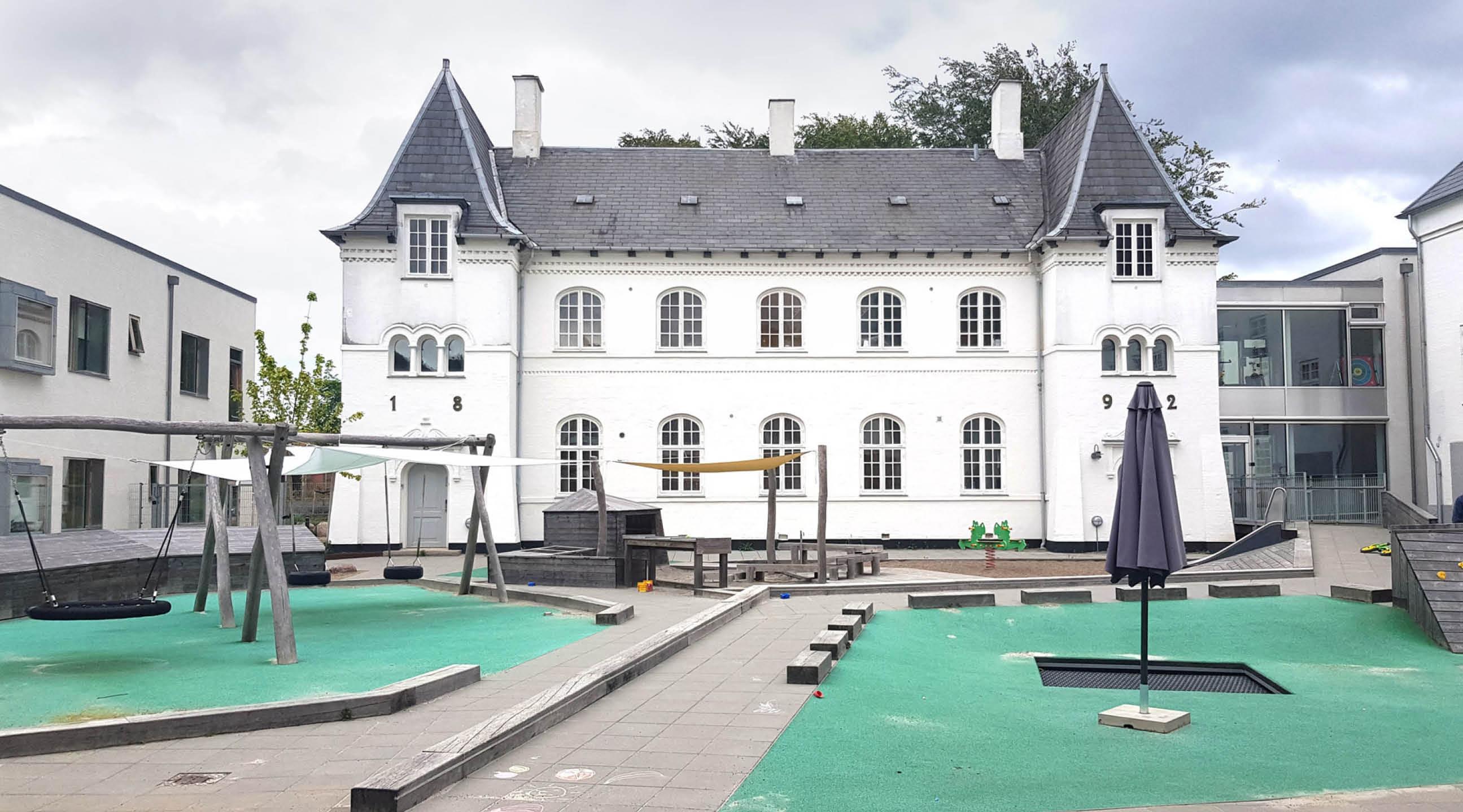 Legeplads med grøn beklædning på jorden og gynger, trampolin og balanceredskaber. I baggrunden et hvidt slot fra 1892.