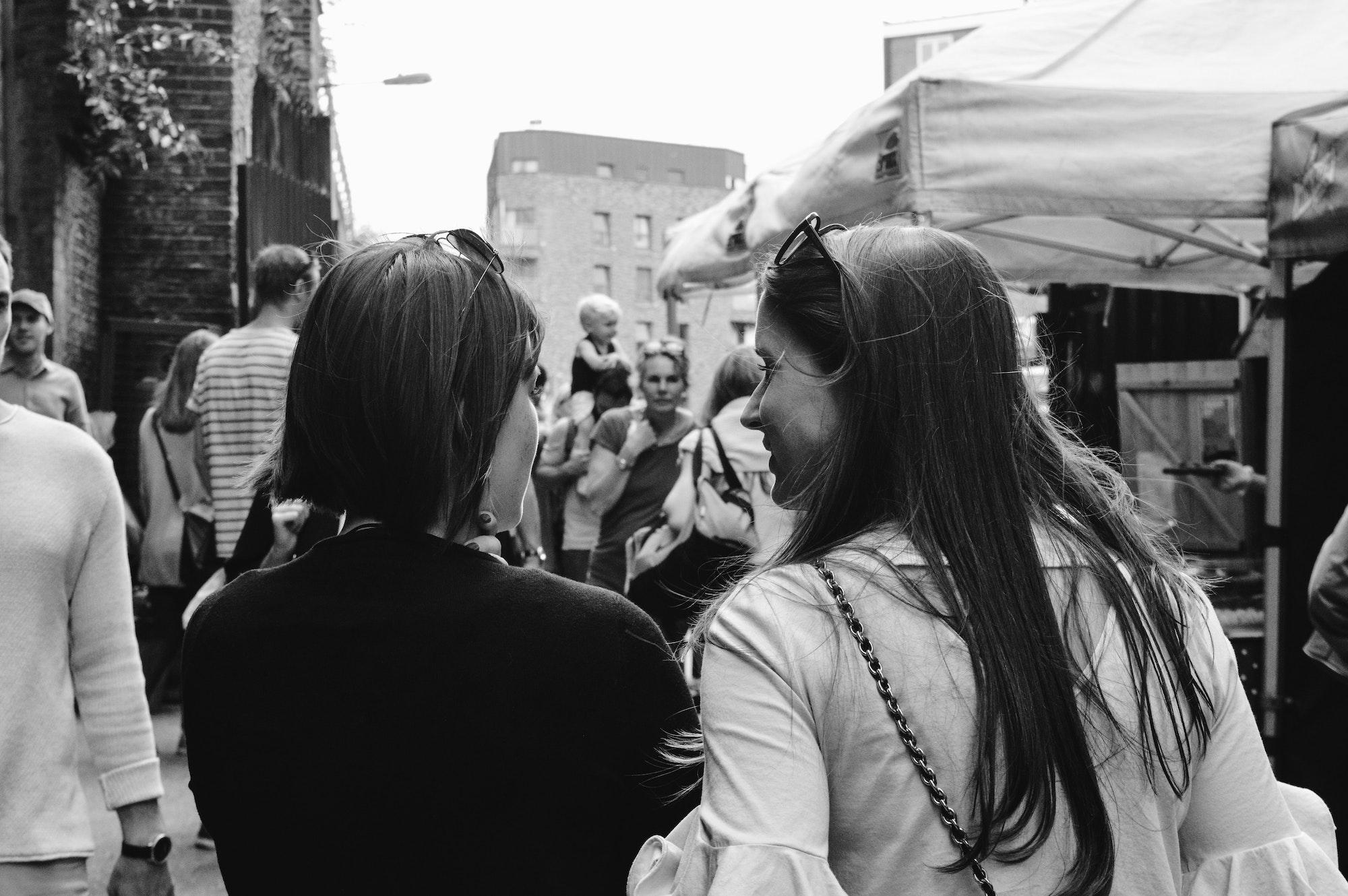 To kvinder fotograferet bagfra i en større menneskemængde