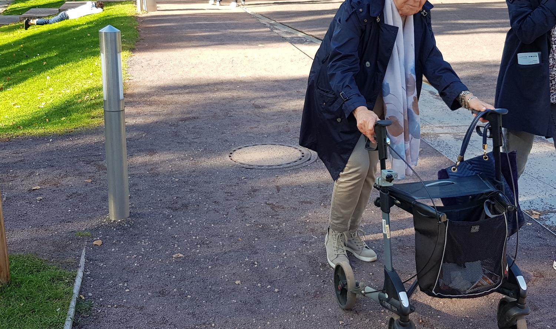 Ældre person går med rollator på stampet grussti