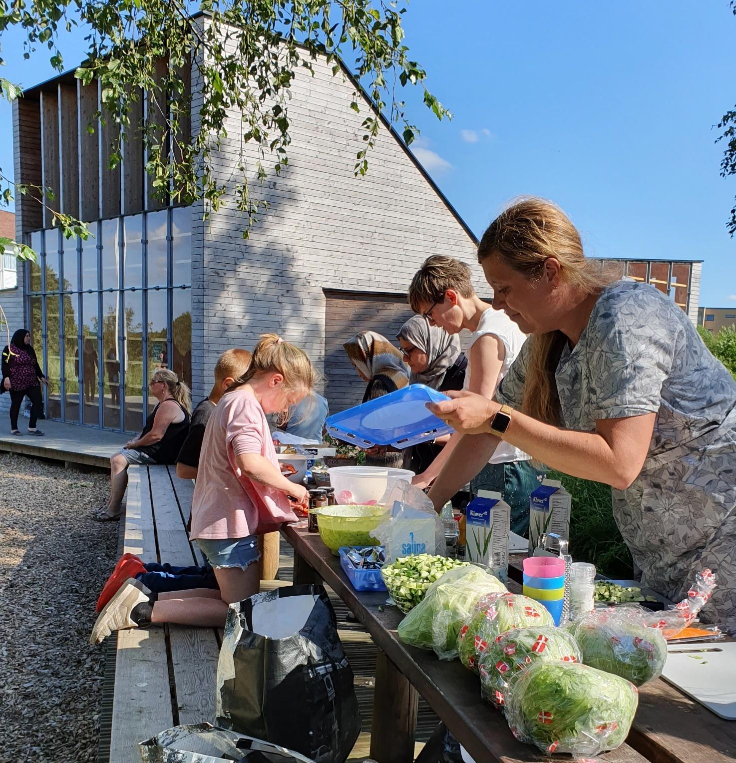 Børn og voksne ved det lange udendørs bord i gang med at forberede mad