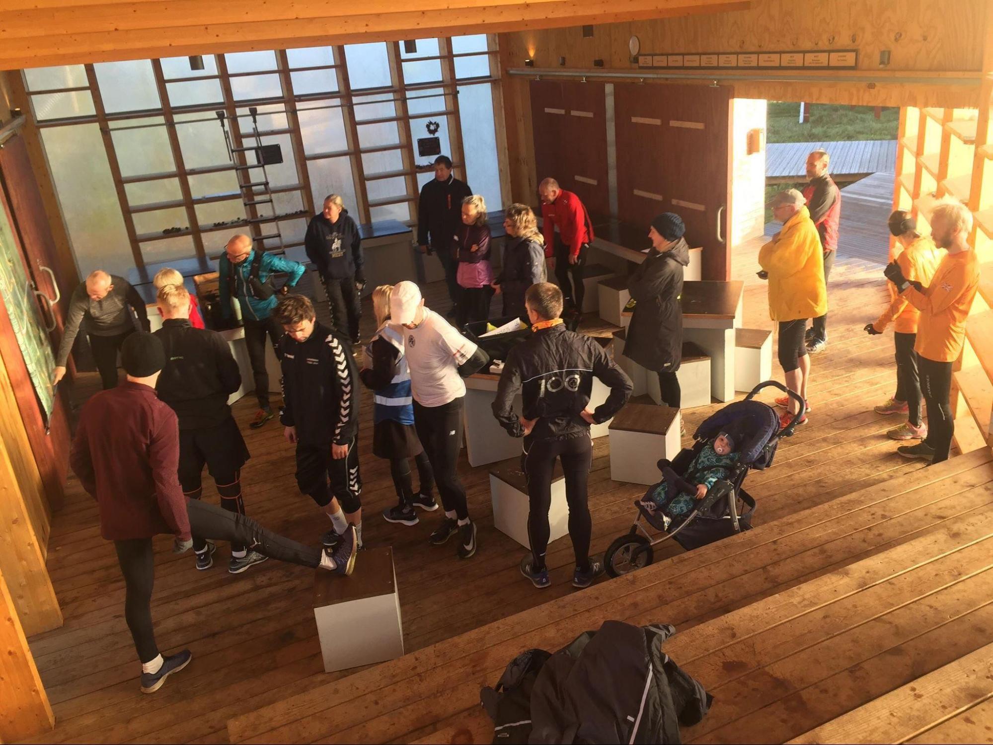 En gruppe voksne løbere og en enkelt barnevogn er forsamlet inde i Myretuen