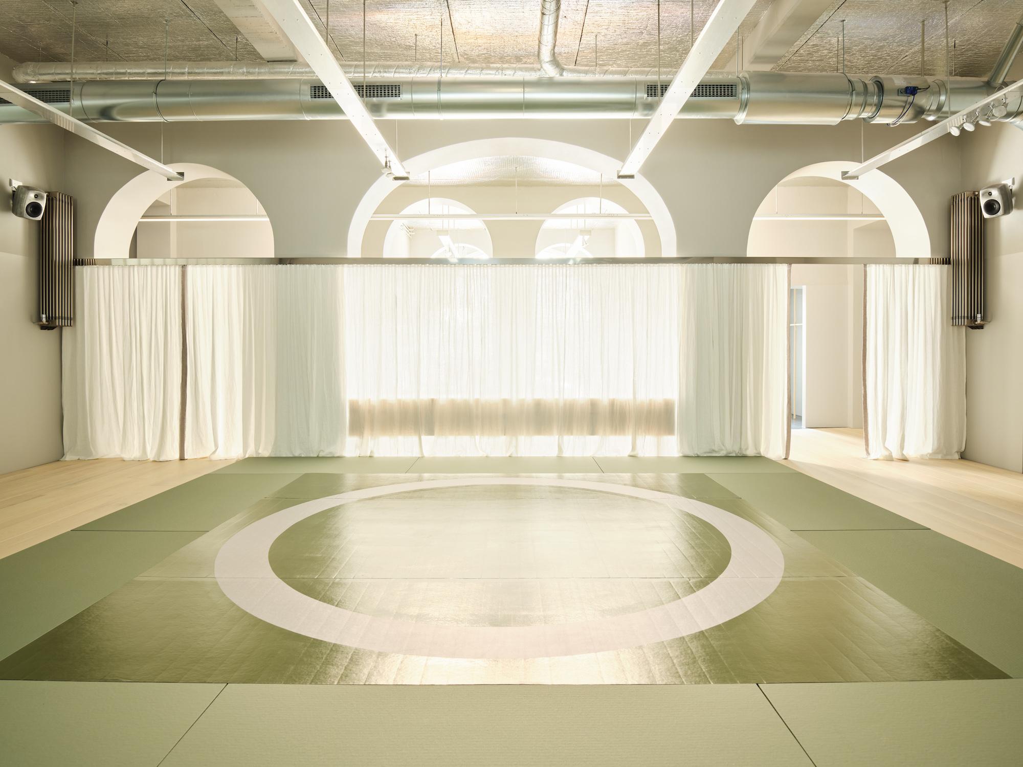 Træningsrummet i Hagius, hvor en stor olivengrøn måtte fylder gulvet og hvide gardiner foran det store vinduesparti skaber et behageligt, blødt lys