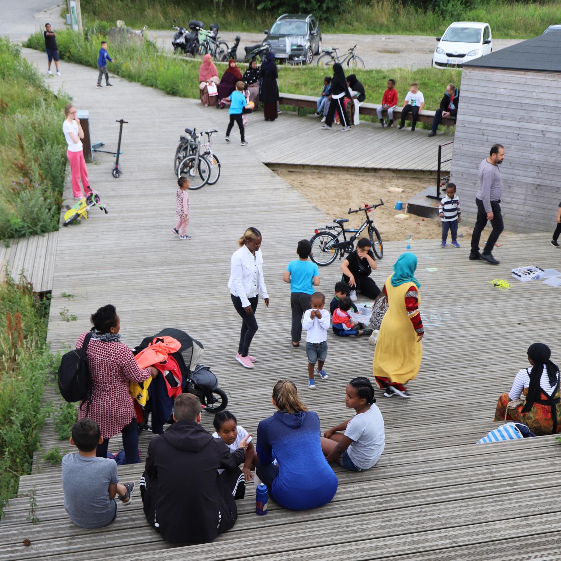 En stor gruppe mennesker, børn som vokse, er forsamlet uden for Myretuen.