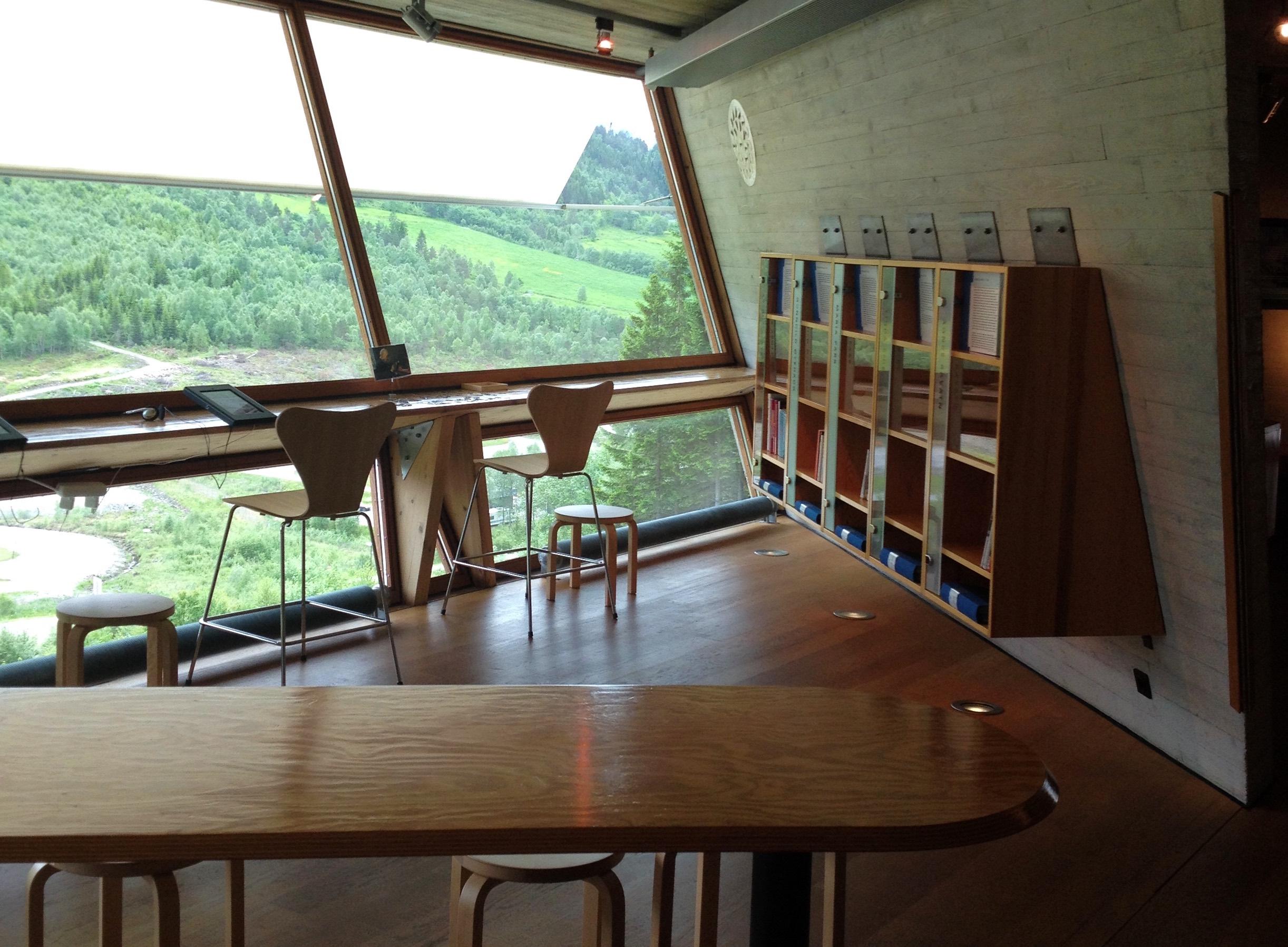 Kontormiljø med stort bord i forgrunden og et højere bord ved vinduet med udsigt ud over et grønt landskab.