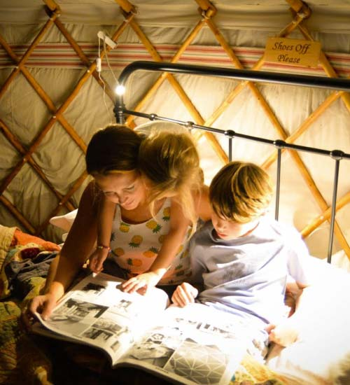Family reading a bed time story inside a luxury yurt