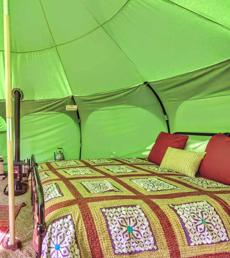 Inside lotus belle tent showing a double bed and stove
