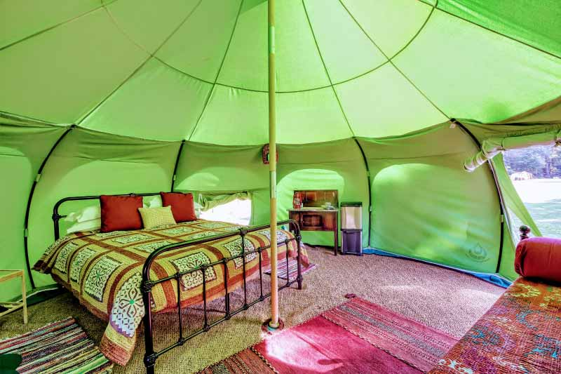 Inside a belle tent showing side table and bed