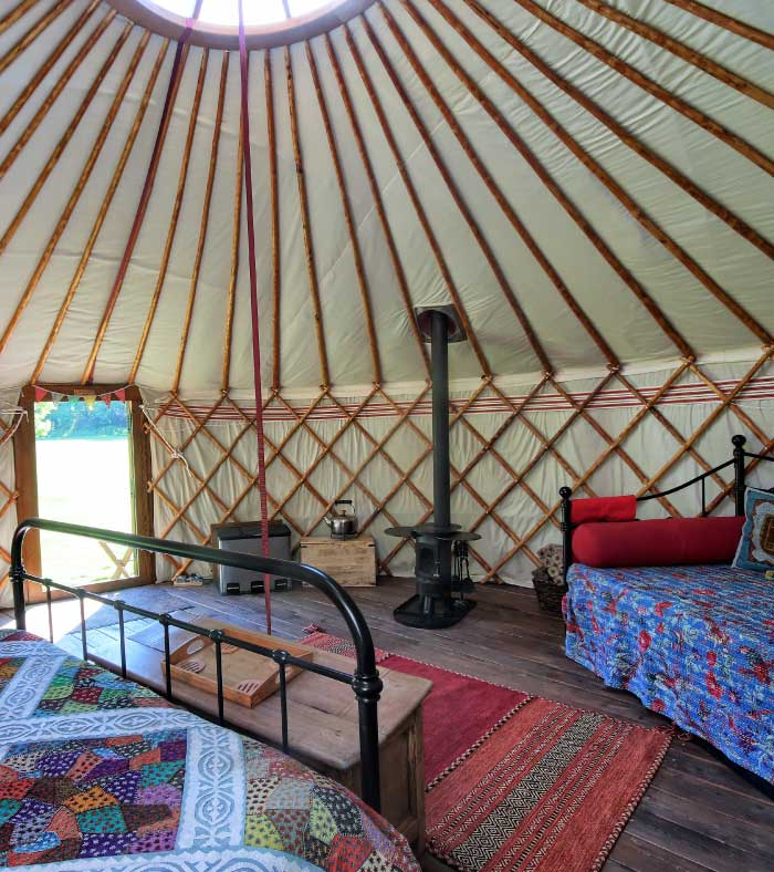 Inside of a luxury yurt showing double bed and stove