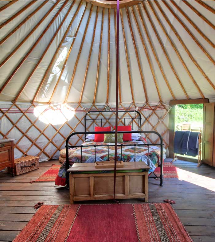 Inside a luxury yurt showing a double bed